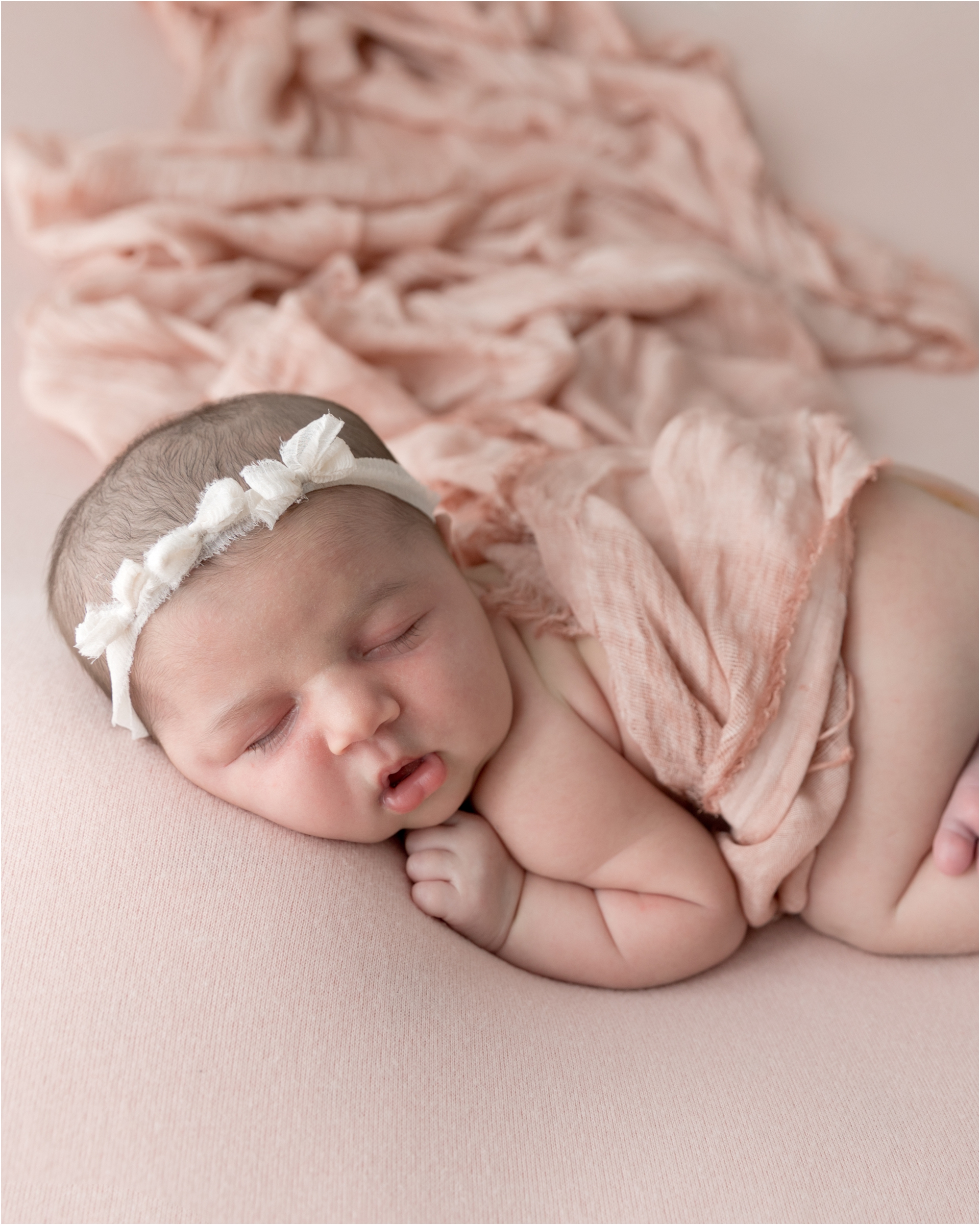 Baby girl on blush pink backdrop during newborn session in Houston studio. Photo by Lifetime of Clicks Photography.