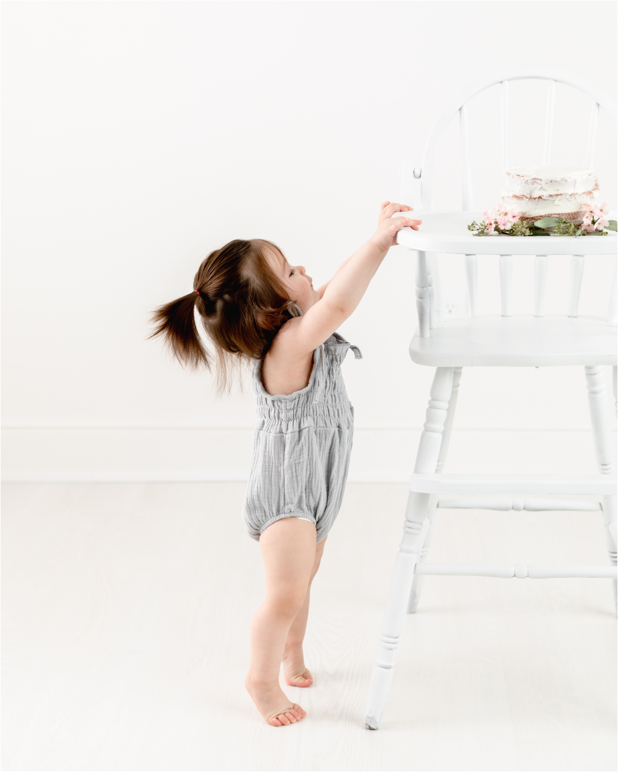Little girl on tippy toes reaching for cake in wooden highchair during cake smash session by Houston baby photographer, Lifetime of Clicks Photography.