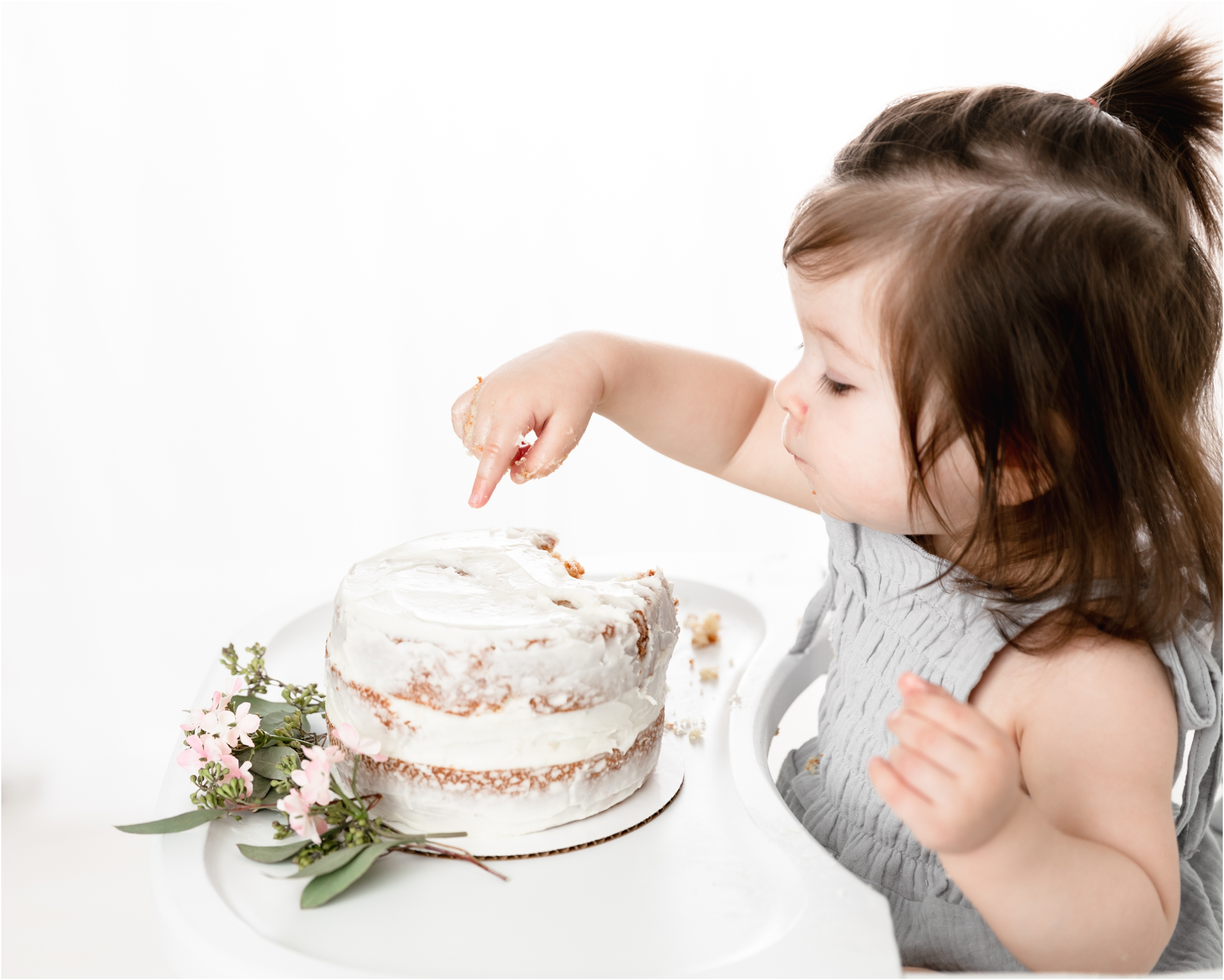 Little girl gently touching frosting on cake during cake smash session with Houston baby photographer, Lifetime of Clicks Photography.
