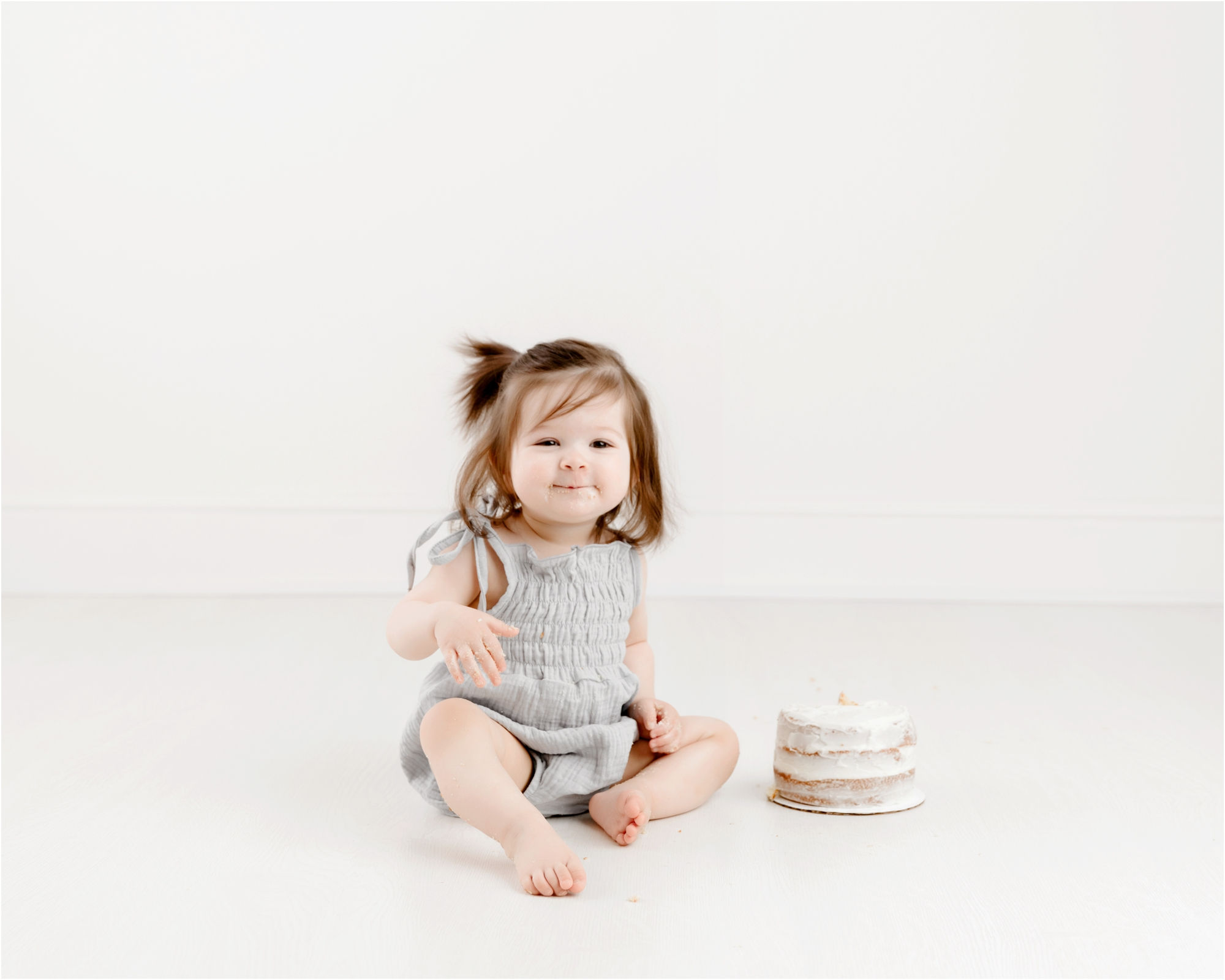 Happy baby tasting frosting during cake smash session with Houston baby photographer, Lifetime of Clicks Photography.
