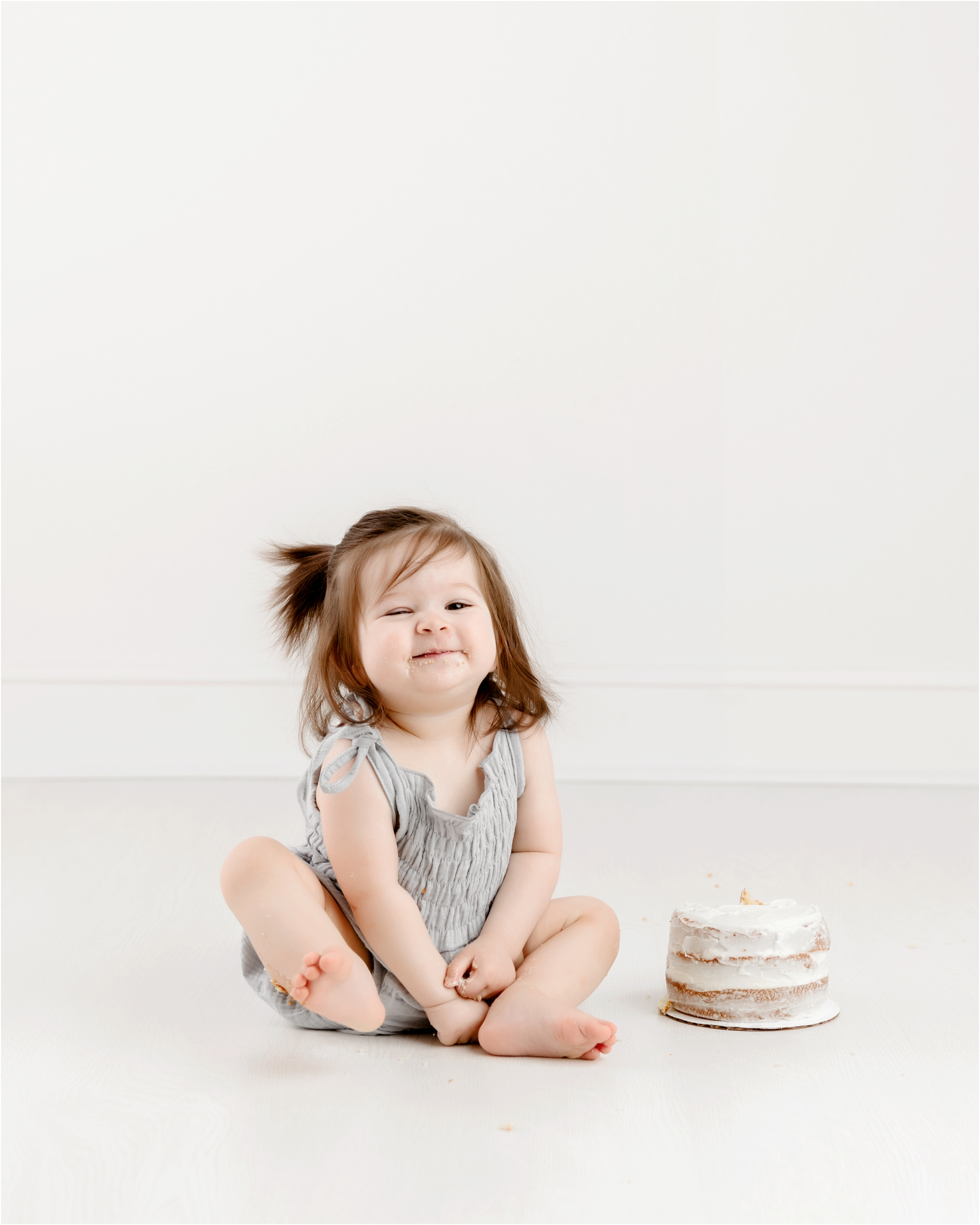 Cute grin from baby girl during cake smash. Photo by Lifetime of Clicks Photography.