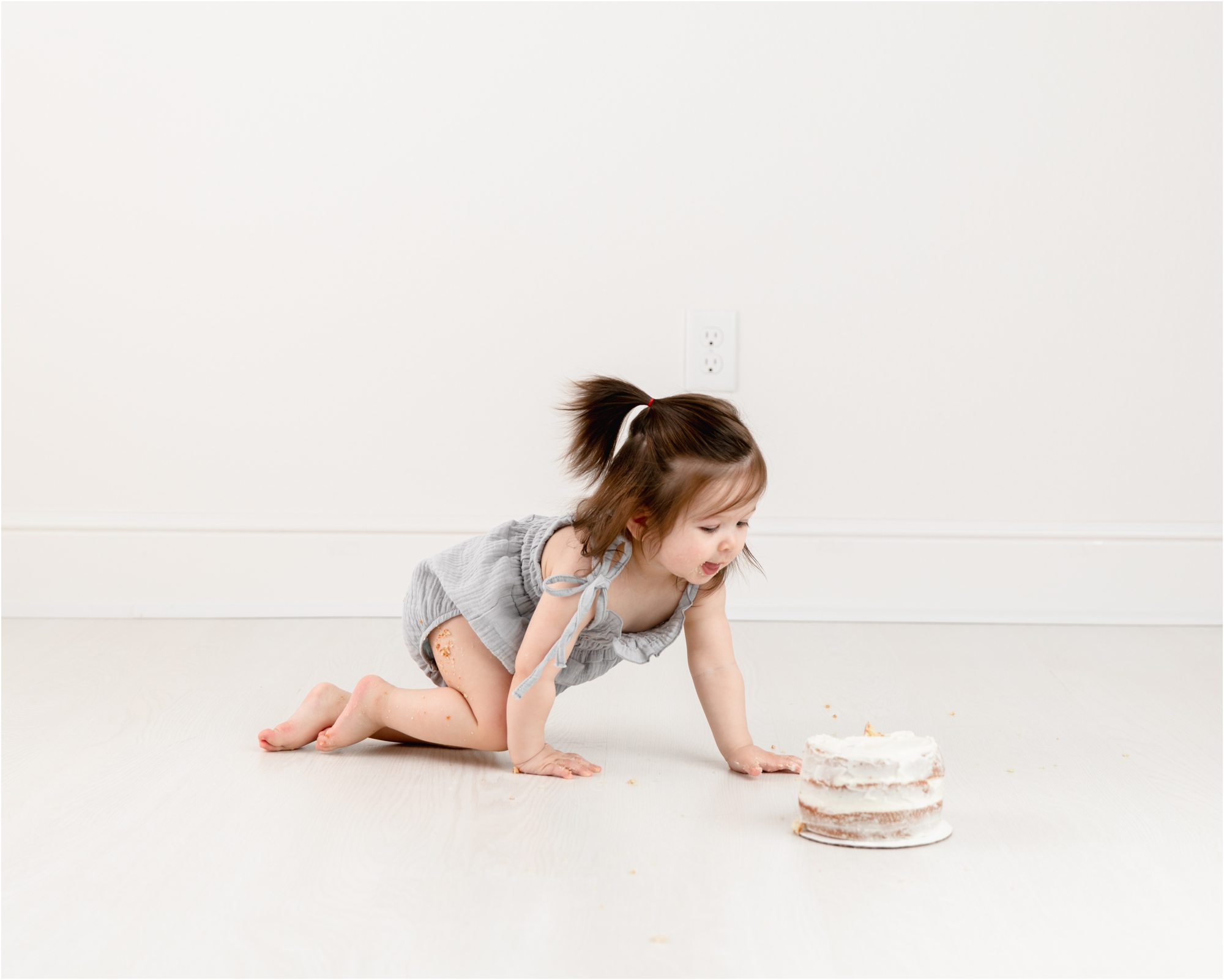Baby crawling to classic white cake during cake smash session in Houston studio. Photo by Lifetime of Clicks Photography.