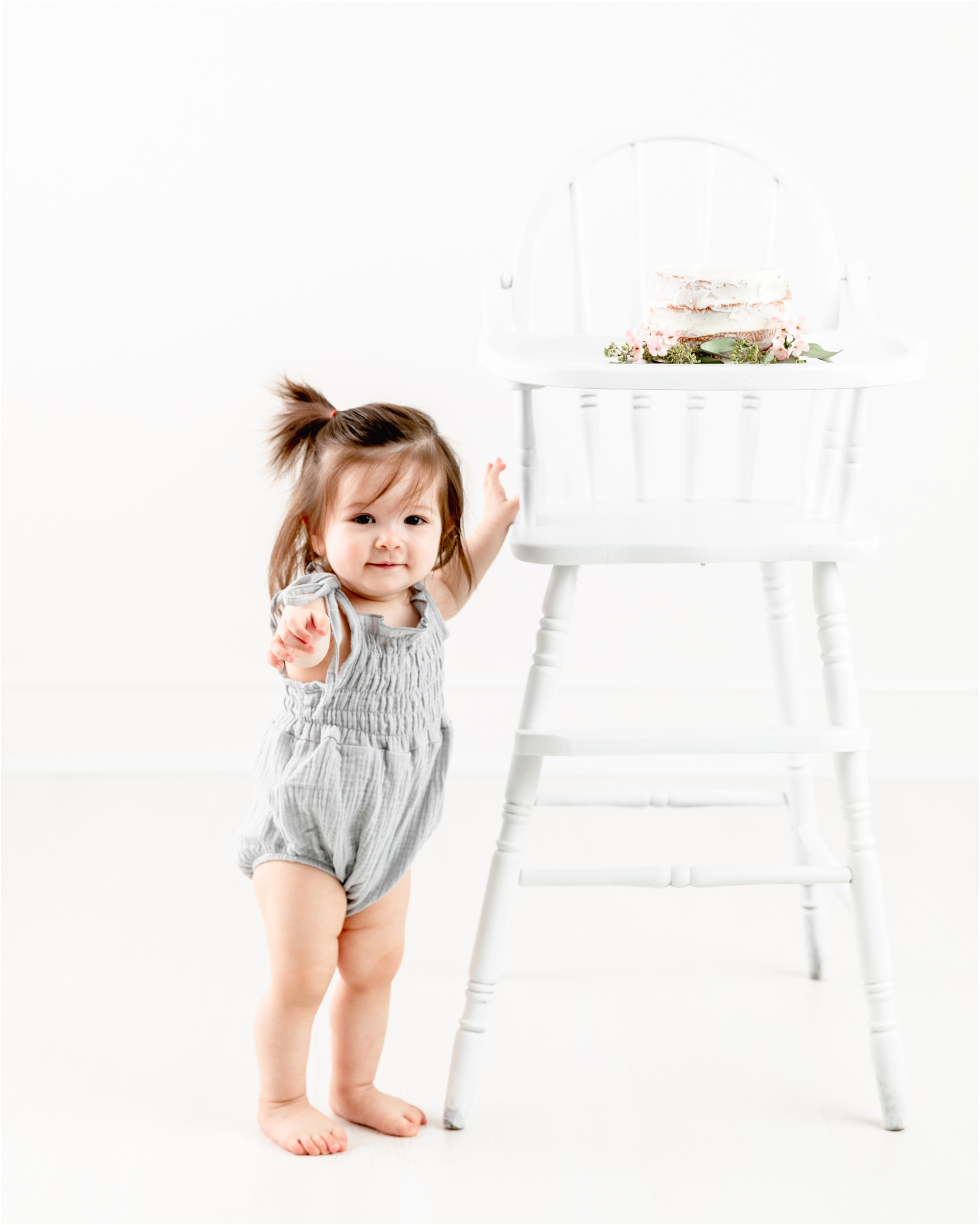 Little girl next to white wooden highchair with classic cake and florals. Photo by Lifetime of Clicks Photography.