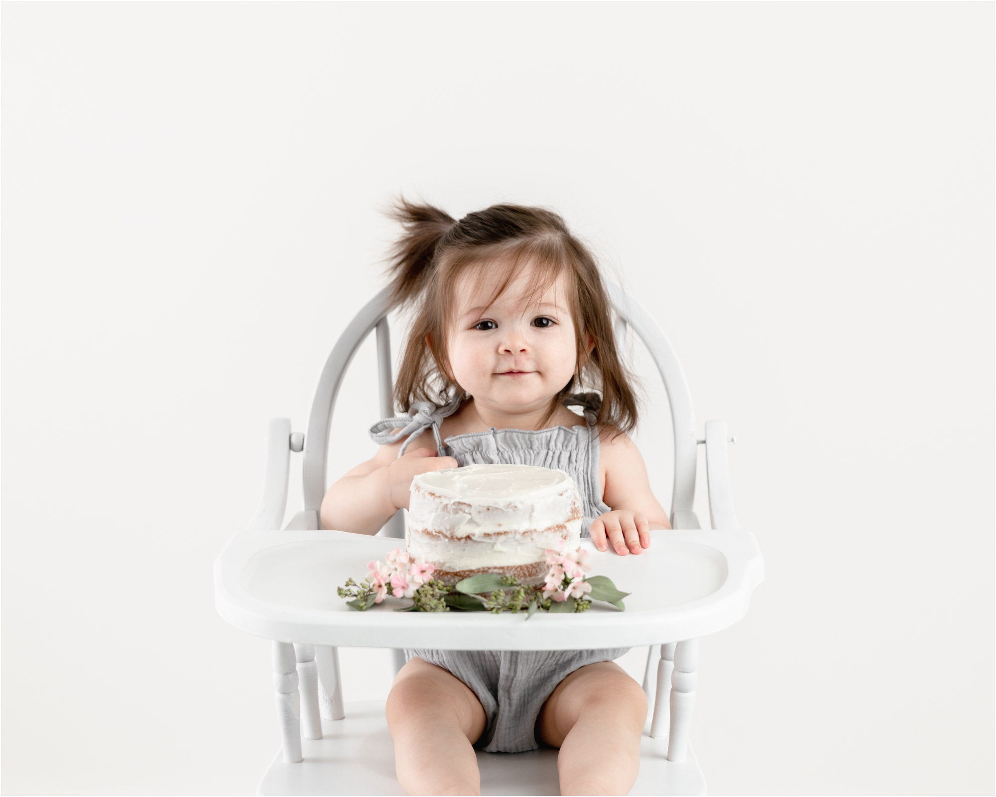 Little girl smiling in highchair with birthday cake and florals. Photo by Lifetime of Clicks Photography.