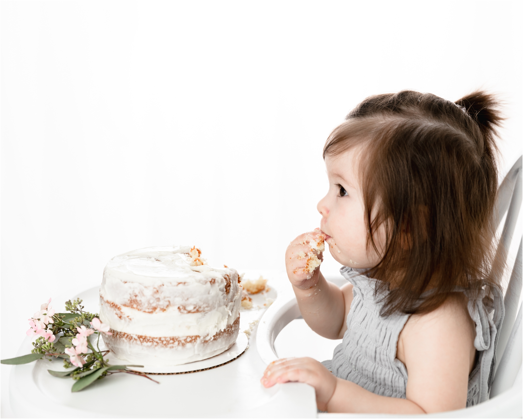 Little girl eating cake in white highchair during classic and simple cake smash session in Houston studio. Photo by Lifetime of Clicks Photography.