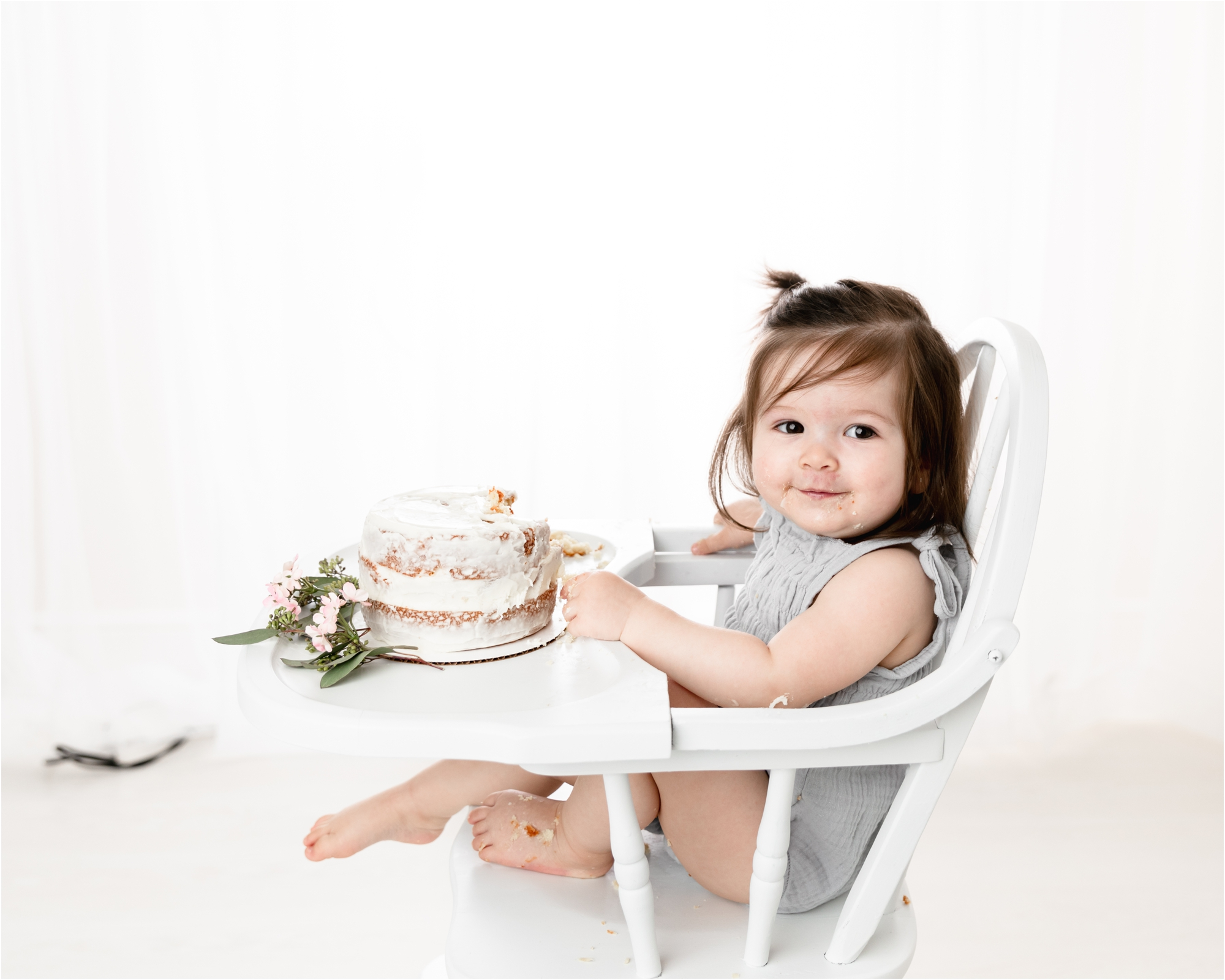 Birthday girl smiling as she eats frosting during cake smash in Houston studio. Photo by Lifetime of Clicks Photography.