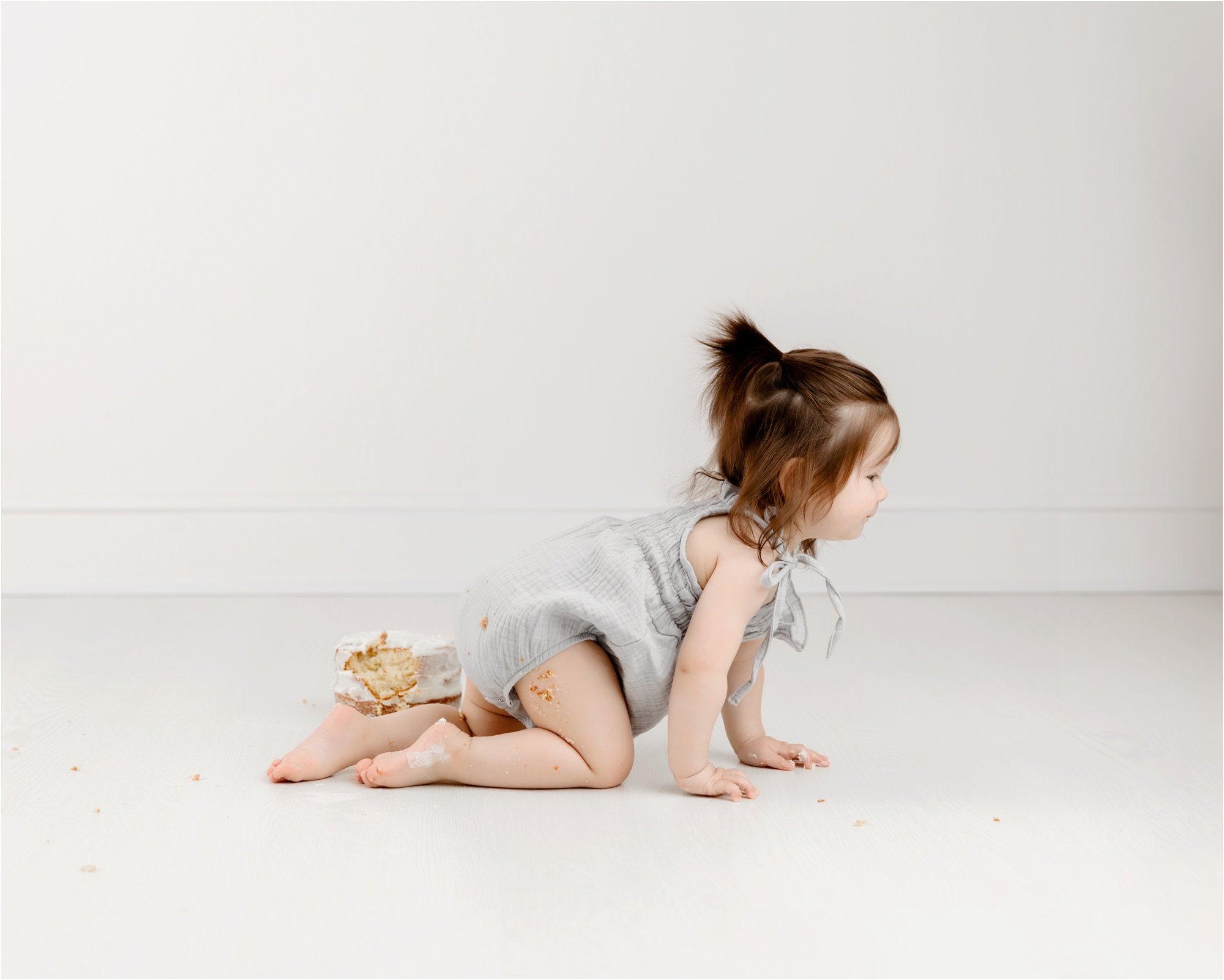 Little girl crawling away from cake smash during studio session with Houston baby photographer, Lifetime of Clicks Photography.