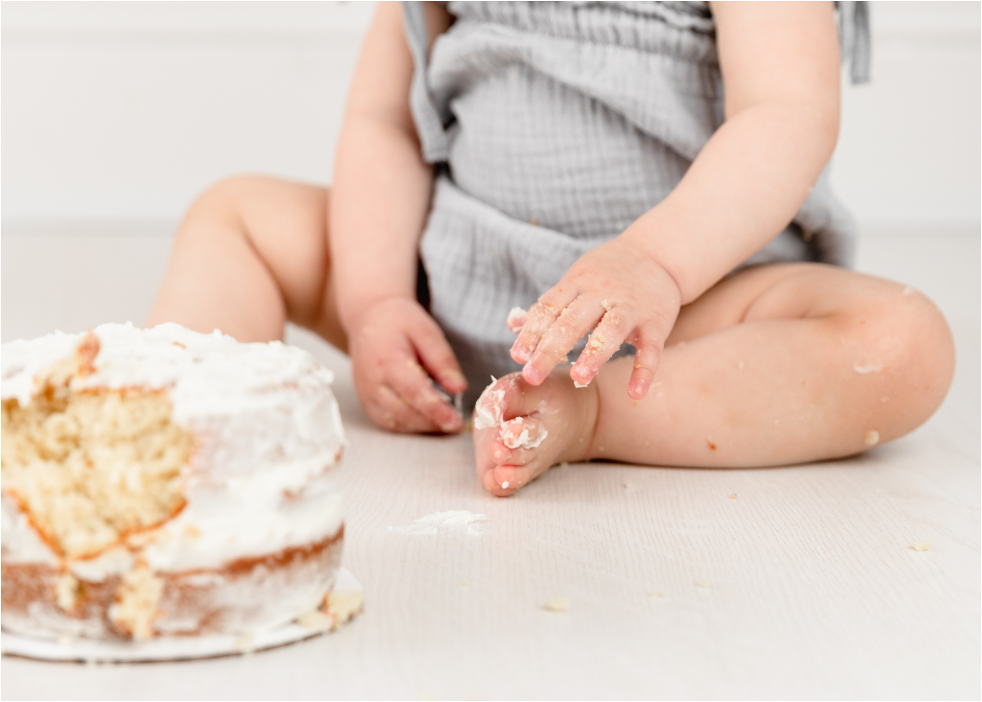 Closeup of baby girl's toes during classic white and grey cake smash session. Photo by Lifetime of Clicks Photography.