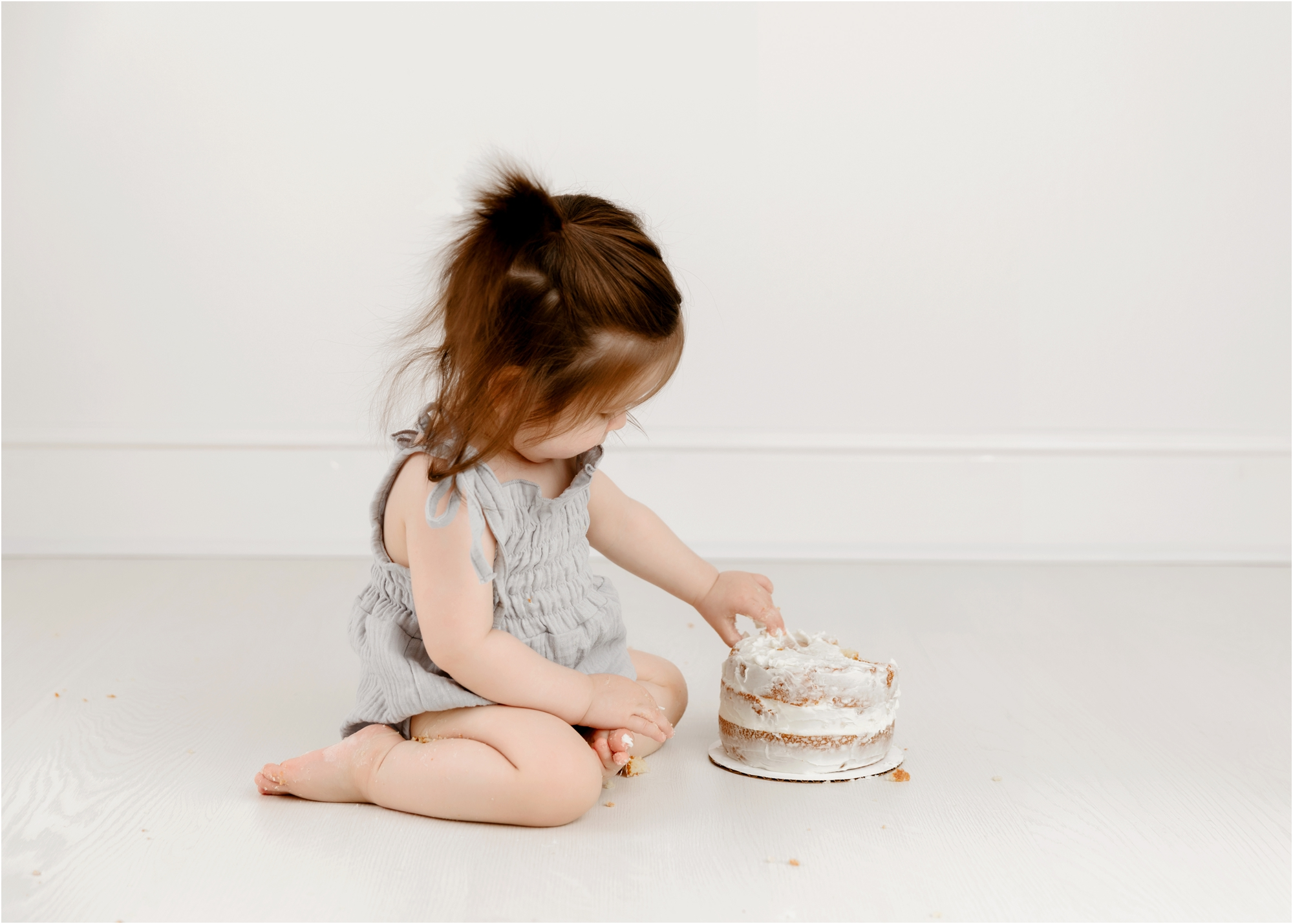Baby gently eating frosting during cake smash session in Houston photography studio. Photo by Lifetime of Clicks Photography.