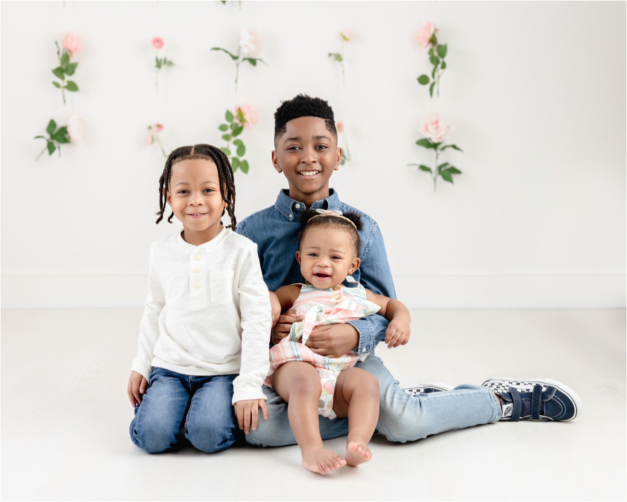 Sweet sibling photo with three kids sitting on floor of studio. Photo by Lifetime of Clicks Photography.
