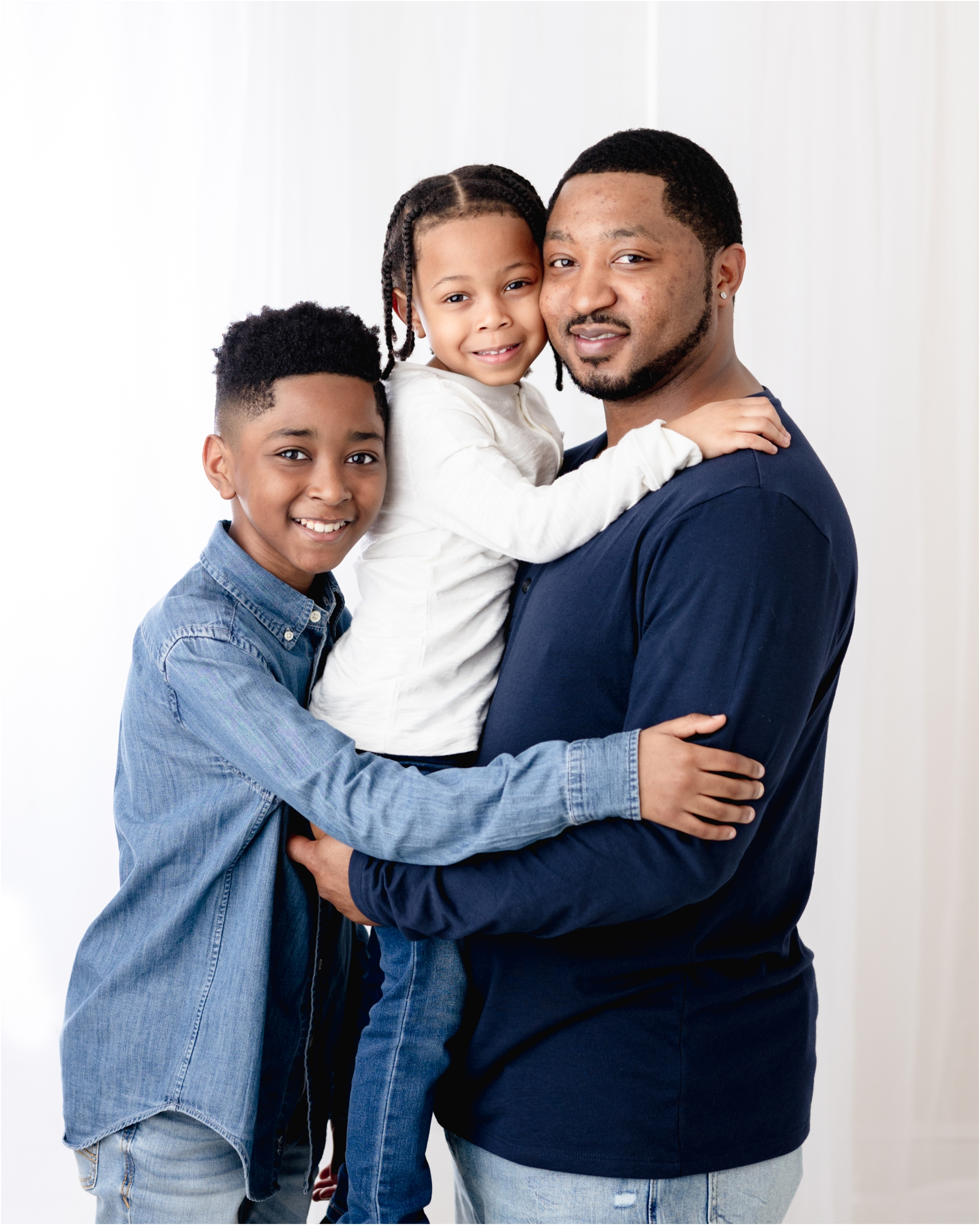 Dad smiling at camera with two sons during studio family photo session in Houston, TX. Photo by Lifetime of Clicks Photography.