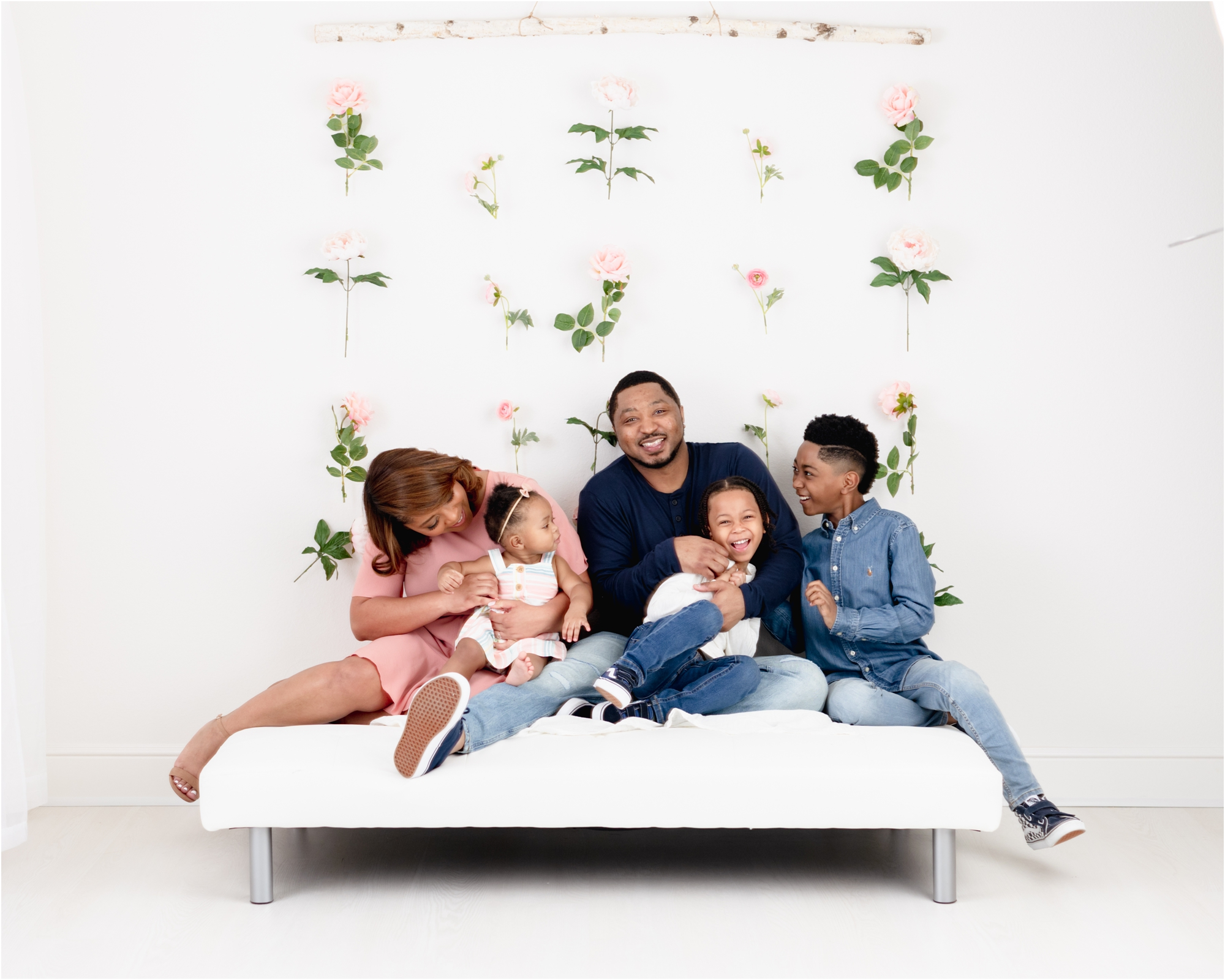 Family of five sitting on bed with floral backdrop during studio session in Houston. Photo by Lifetime of Clicks Photography.