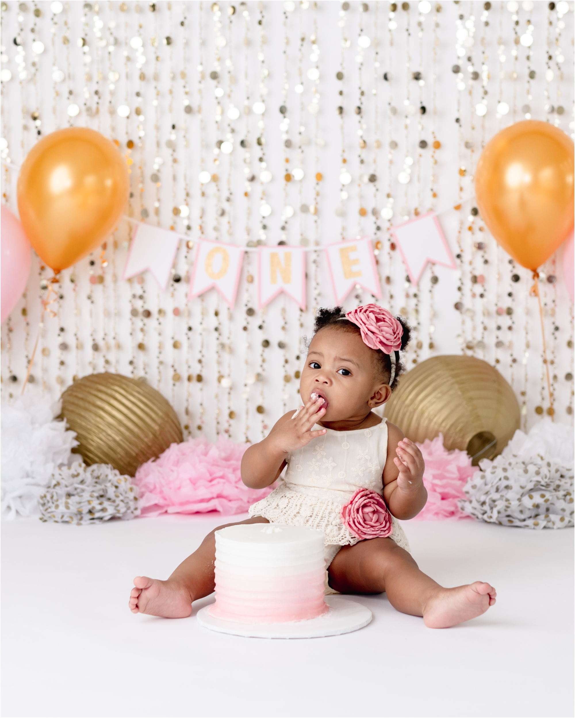 Baby girl tasting frosting during pink and gold themed cake smash session. Photo by Lifetime of Clicks Photography.