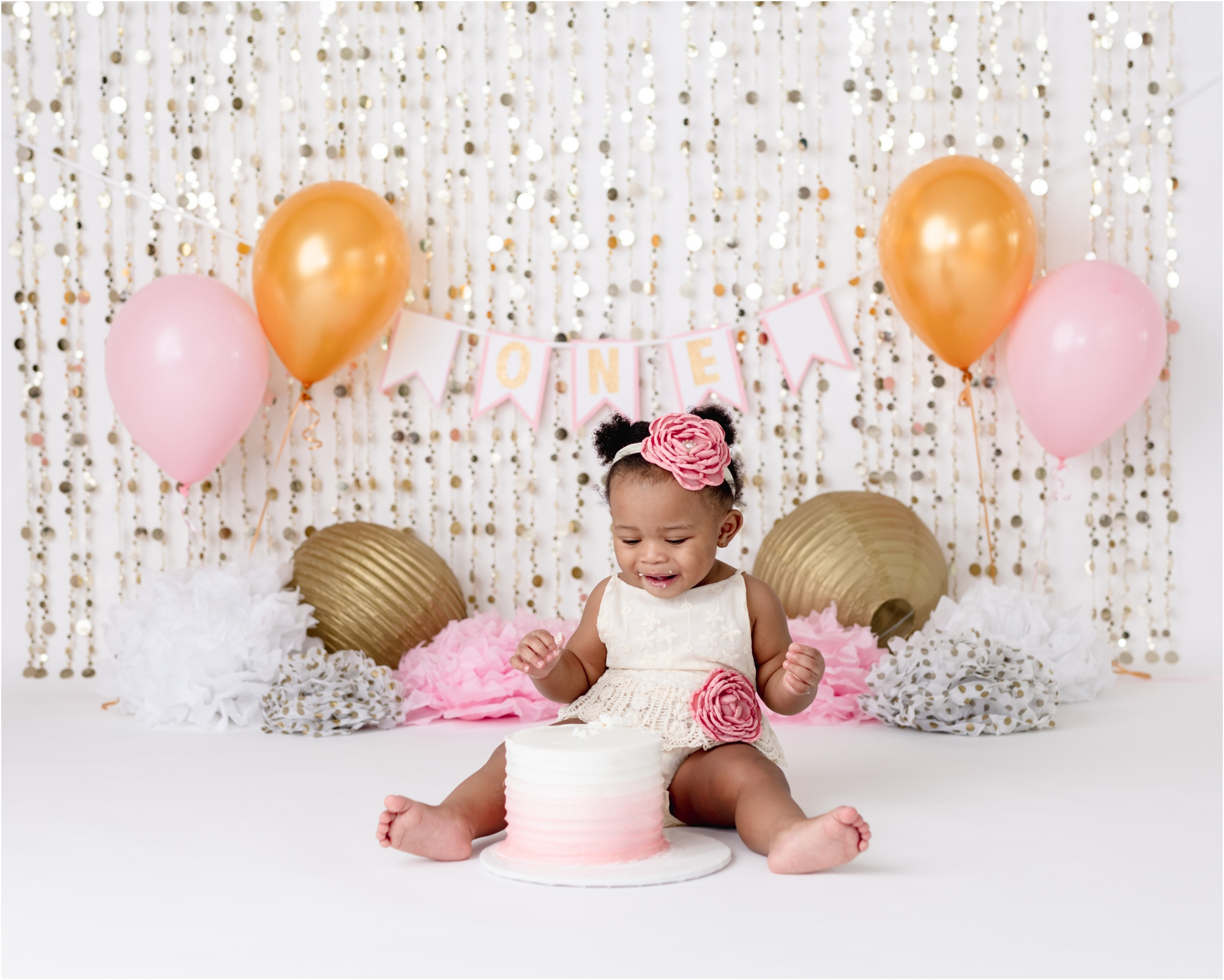 Baby girl smiling during cake smash photoshoot with pink and gold balloons and ombre cake. Photo by Houston cake smash photographer, Lifetime of Clicks Photography.