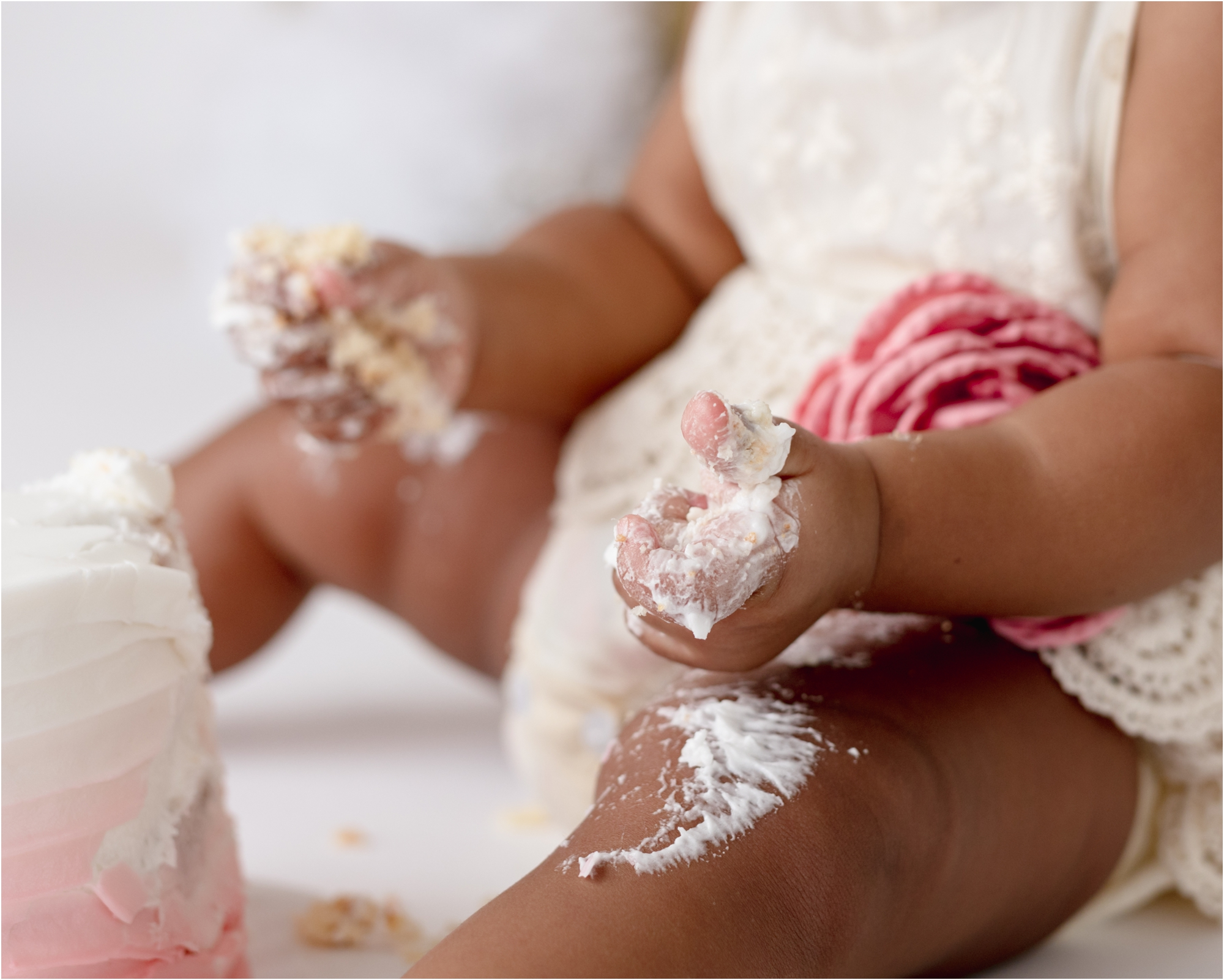 Closeup of frosting on baby girl's hands during cake smash session. Photo by Lifetime of Clicks Photography.