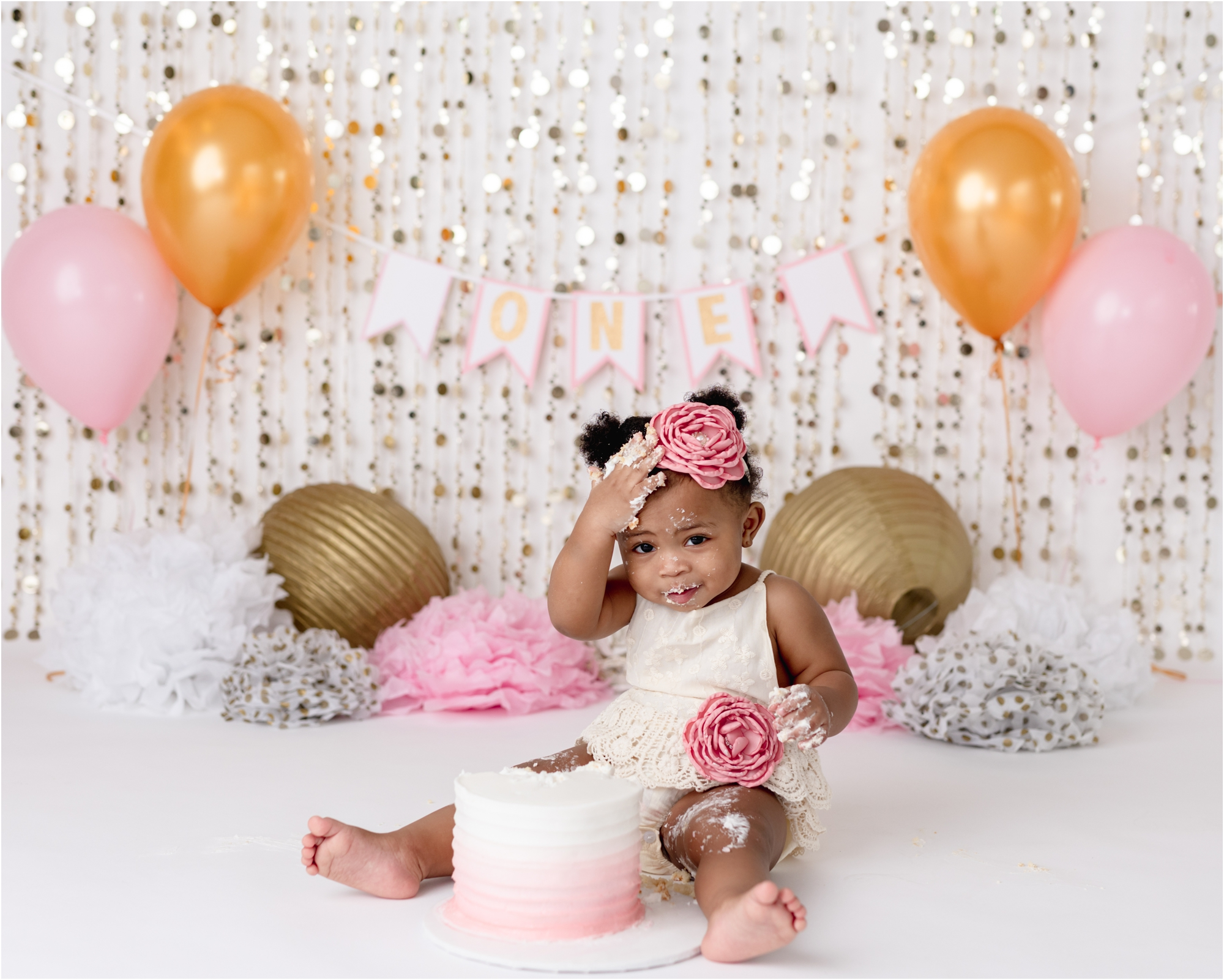 Little girl covered in frosting during cake smash photoshoot in Houston with pink and gold decor. Photo by Lifetime of Clicks Photography.