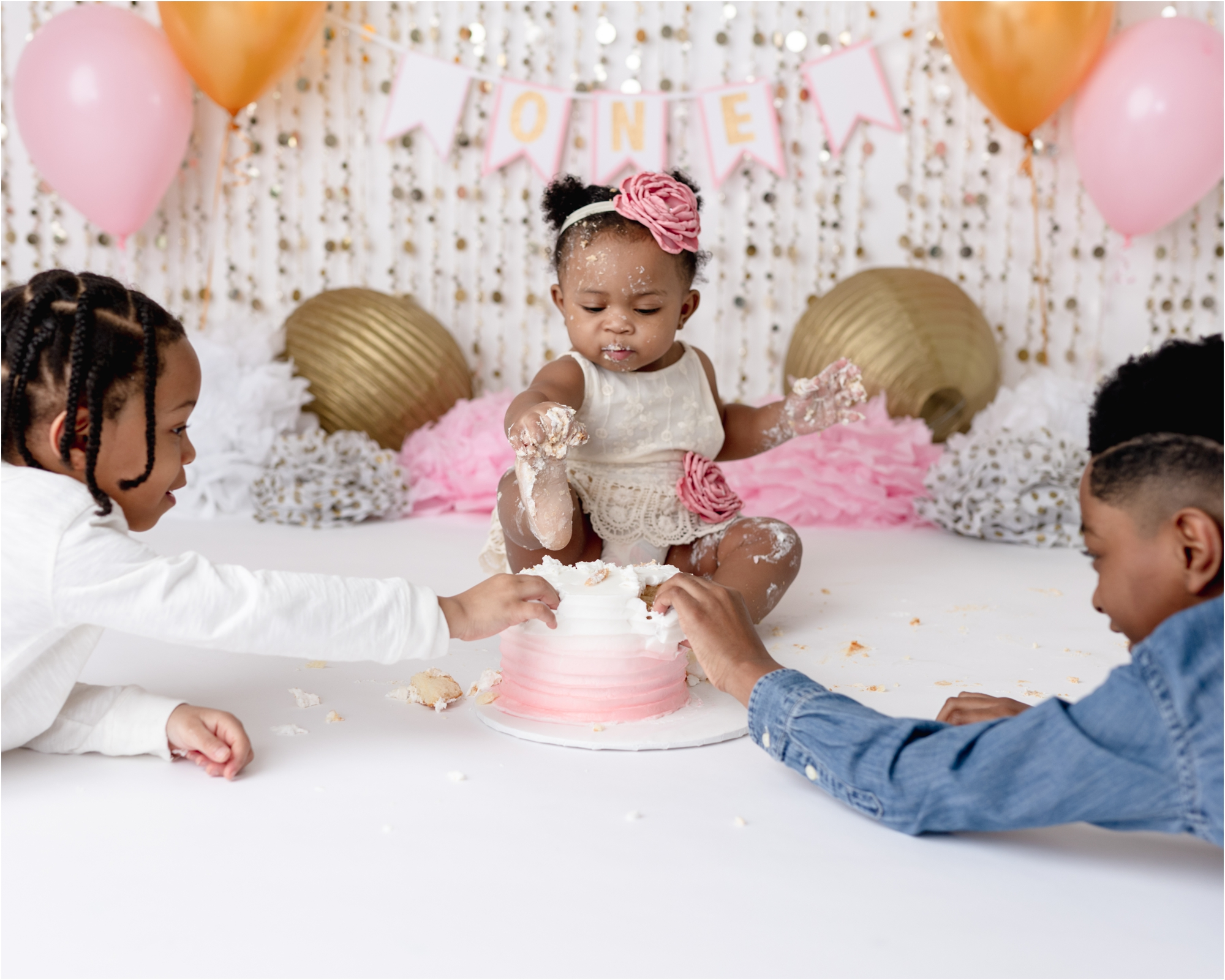Baby girl with frosting on toes during cake smash photoshoot in Houston studio. Photo by Lifetime of Clicks Photography.