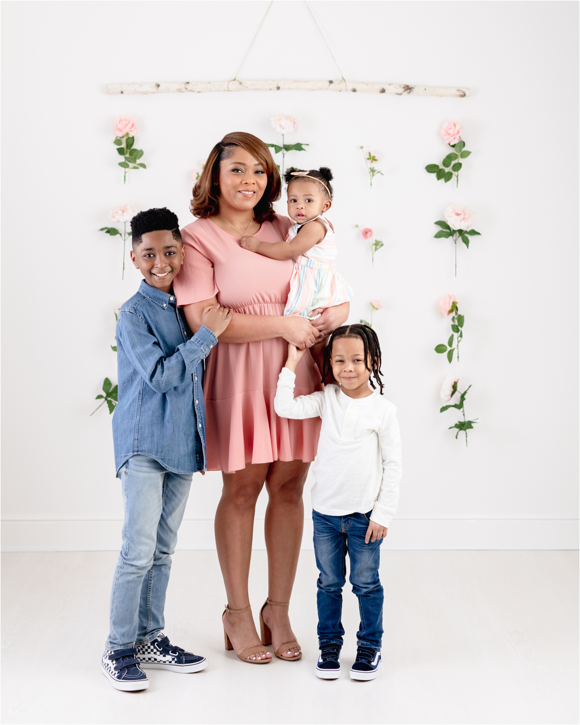 Mom smiling at camera with three children during studio family session with floral backdrop. Photo by Lifetime of Clicks Photography.