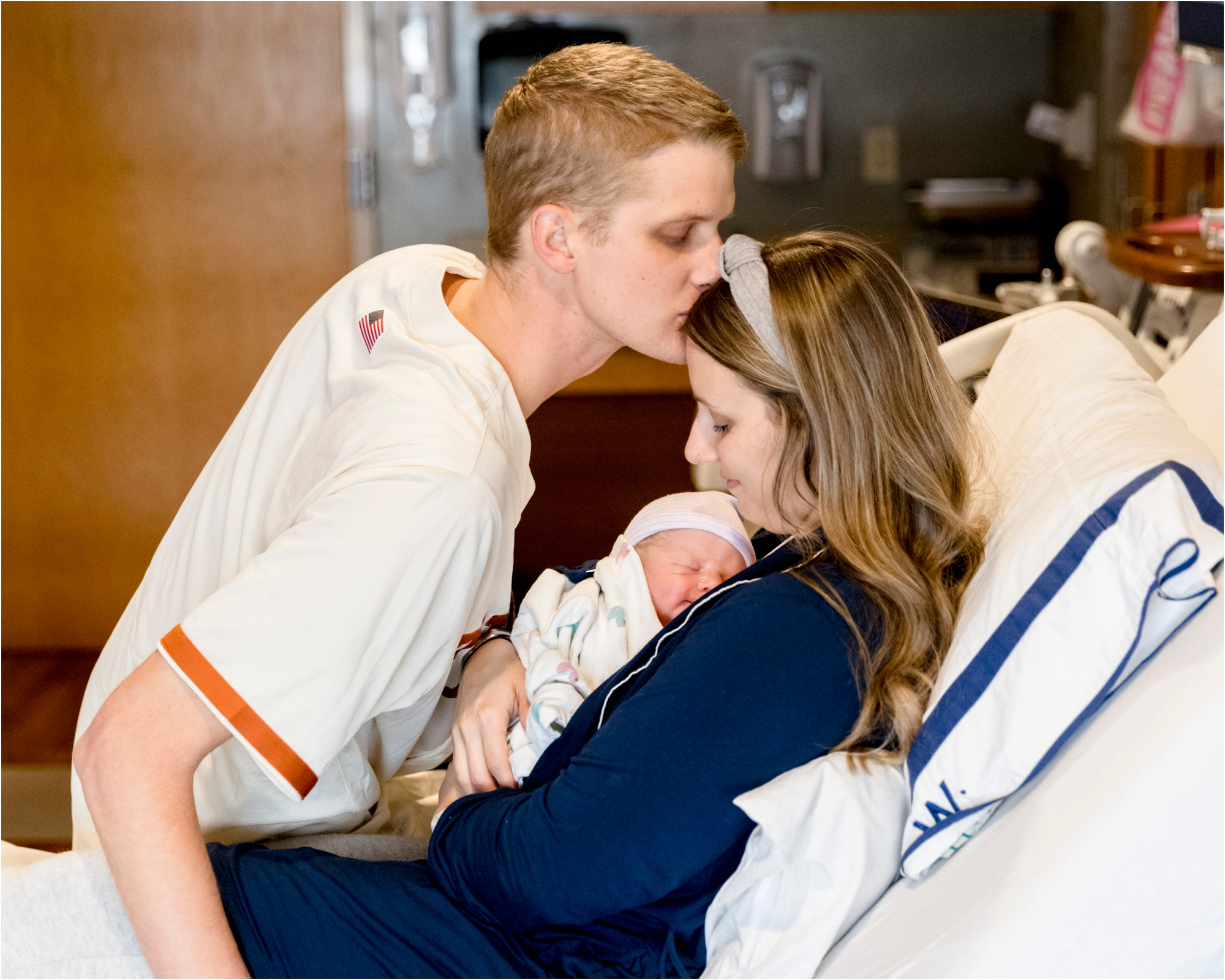 Dad kissing Mom's forehead as she holds baby in hospital room. Photo by Lifetime of Clicks Photography.