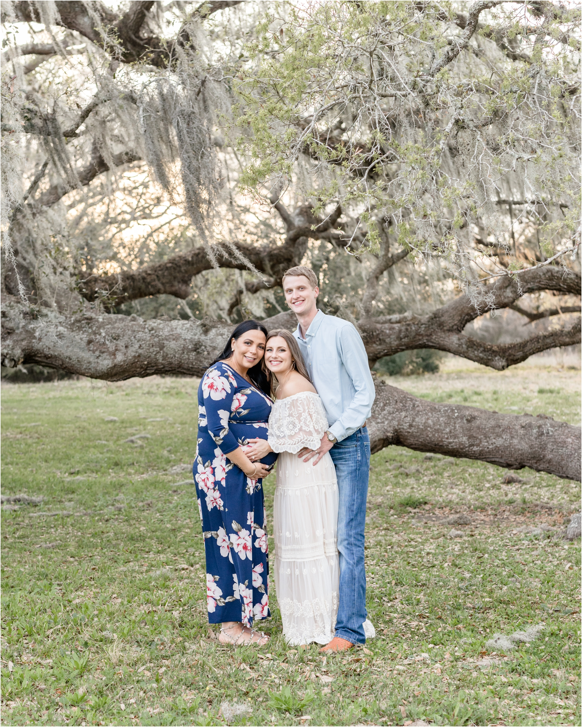 Couple with surrogate mother smiling at camera under moss-covered tree in Houston, TX area. Photo by Houston maternity photographer, Lifetime of Clicks Photography.
