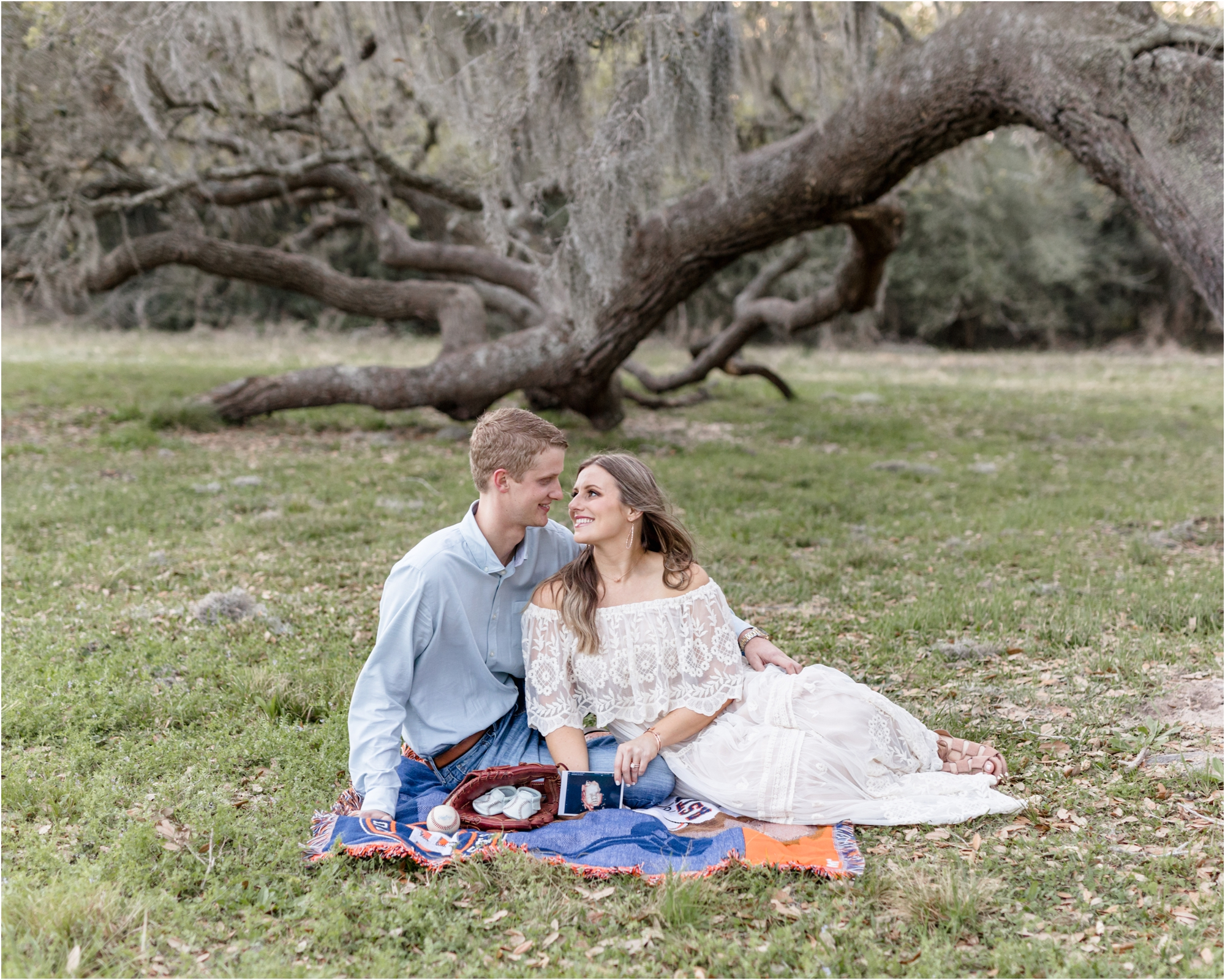 Parents sitting on blanket with ultrasound image under moss-covered tree in Houston, TX. Photo by Lifetime of Clicks Photography.