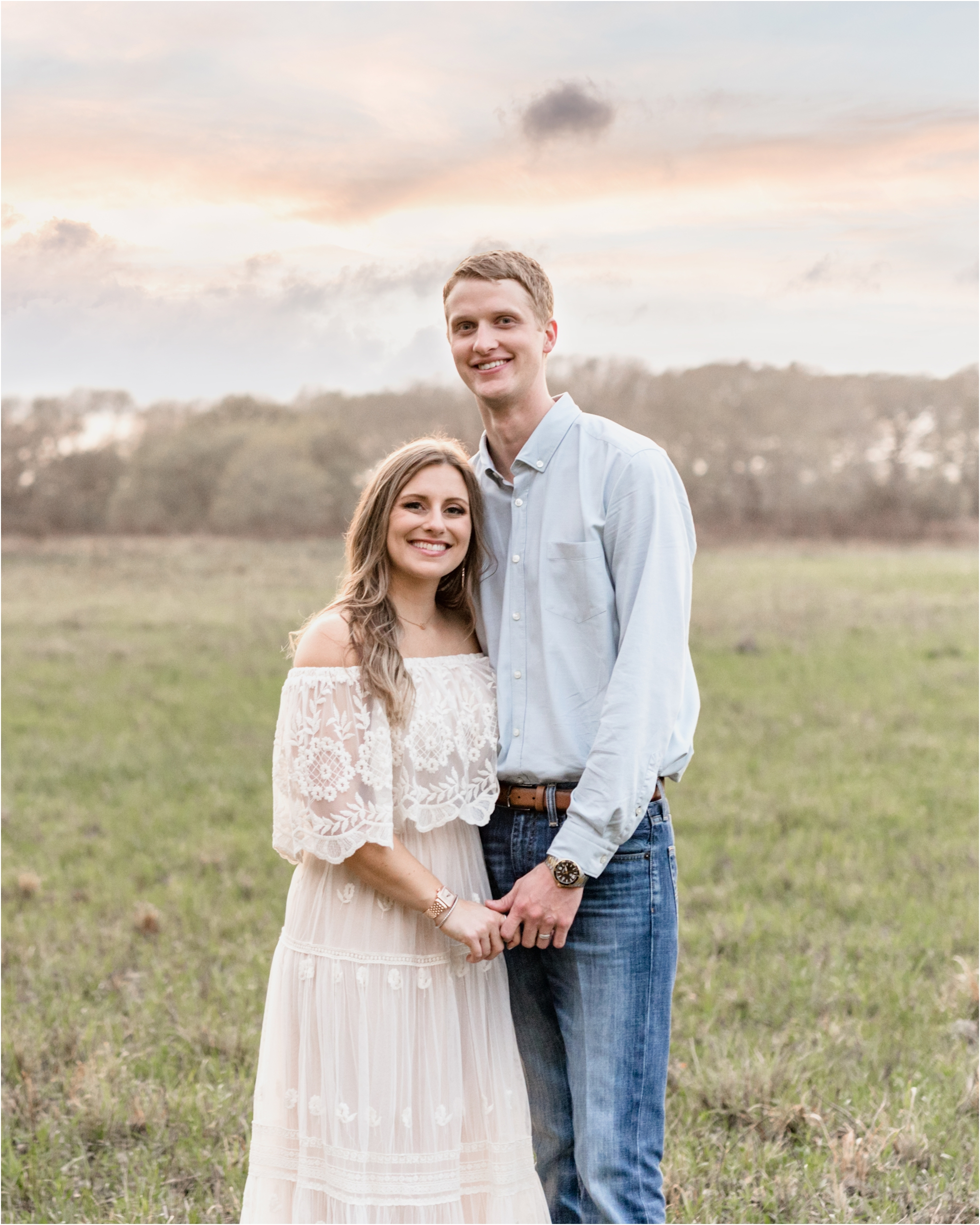 Husband and wife smiling at camera during sunset field session by Houston surrogate maternity photographer, Lifetime of Clicks Photography.