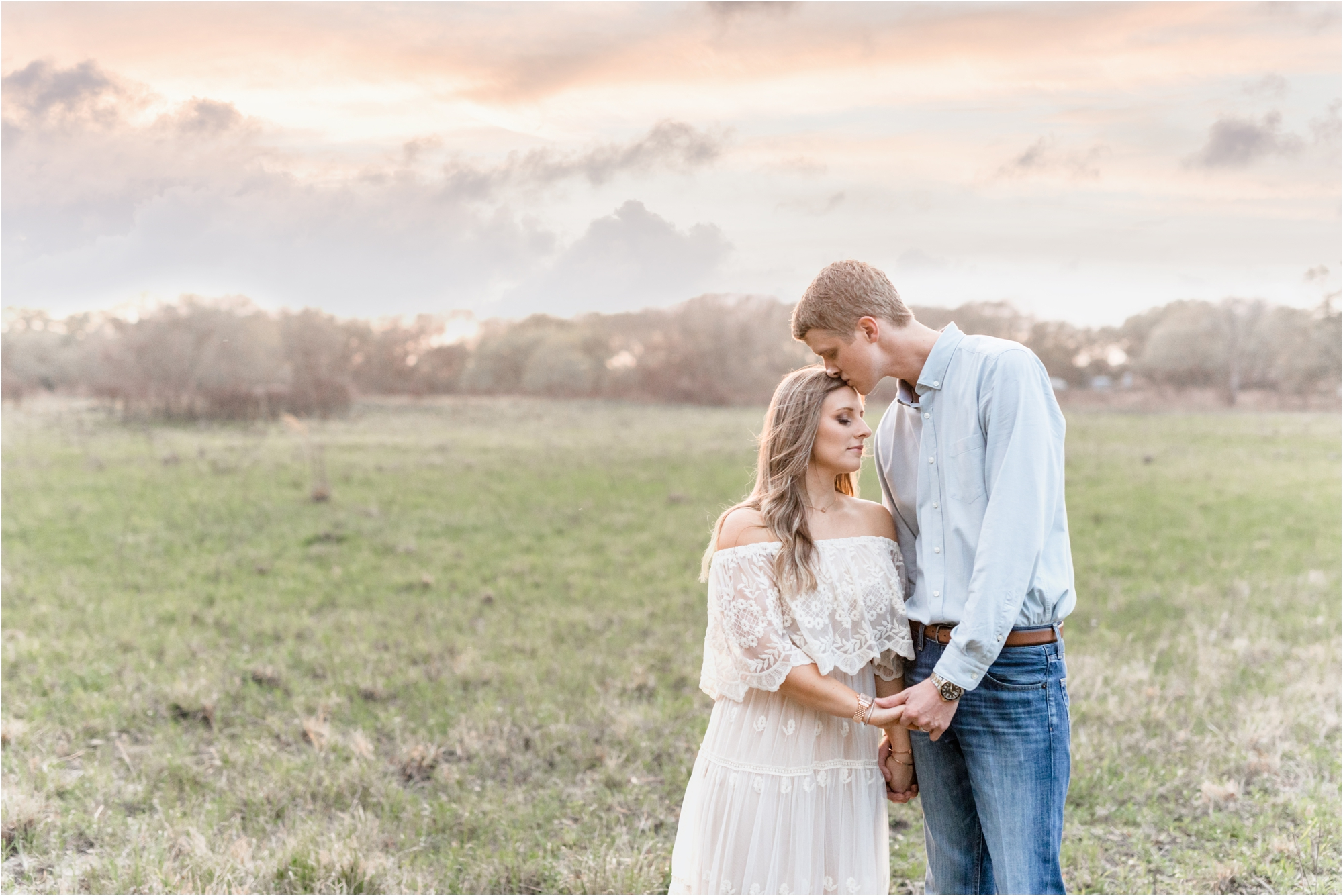 Husband kissing wife's forehead during sunset session in beautiful field. Photo by Lifetime of Clicks Photography.