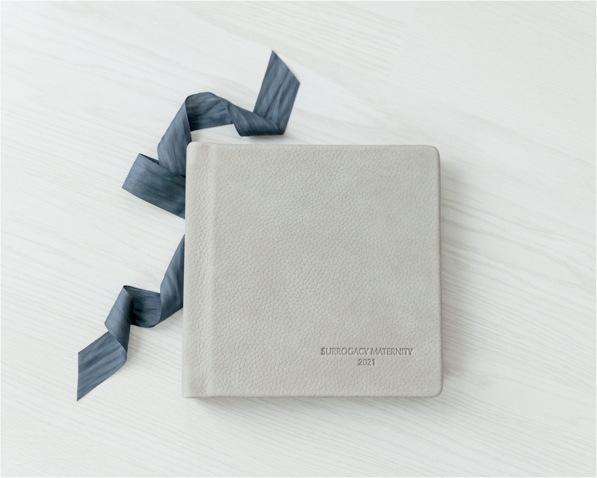 Cover of grey leather heirloom album for surrogate maternity session designed by Houston maternity photographer, Lifetime of Clicks Photography.