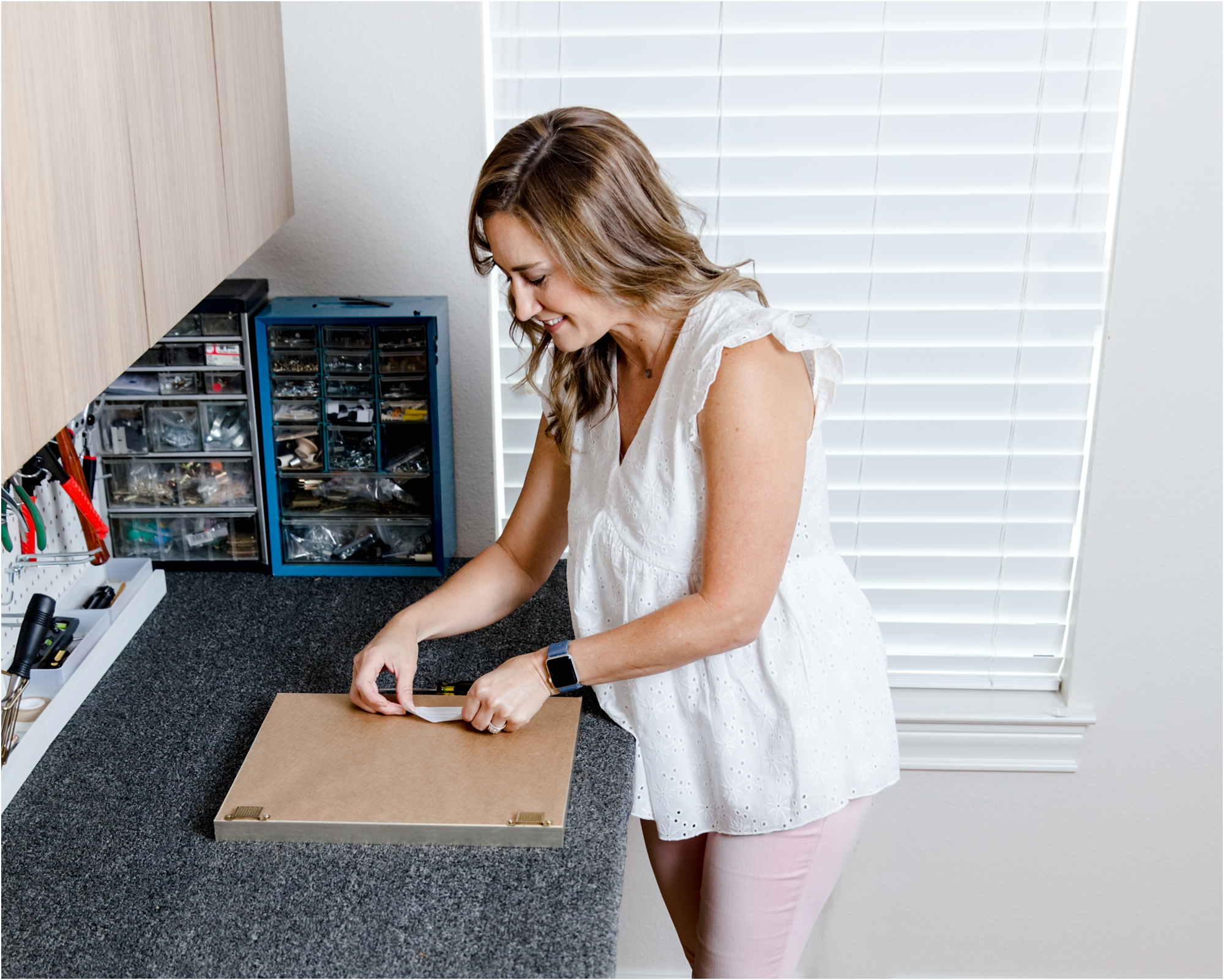 Kelly putting final touches on custom framed portrait in her Katy, TX studio. Photo and service provided by Lifetime of Clicks Photography.