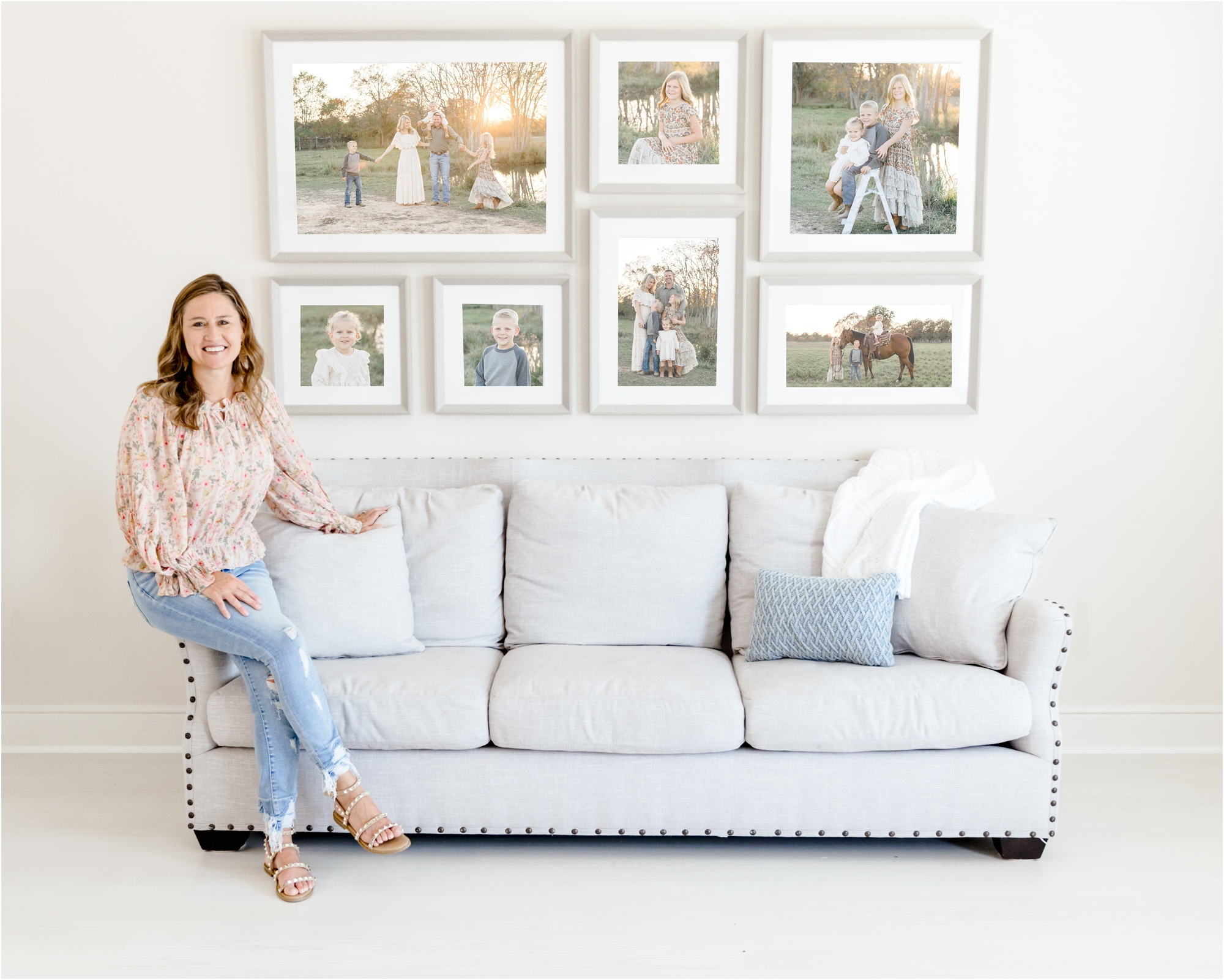 Image of full service newborn and family photographer, Kelly of Lifetime of Clicks Photography, in studio with large gallery wall.