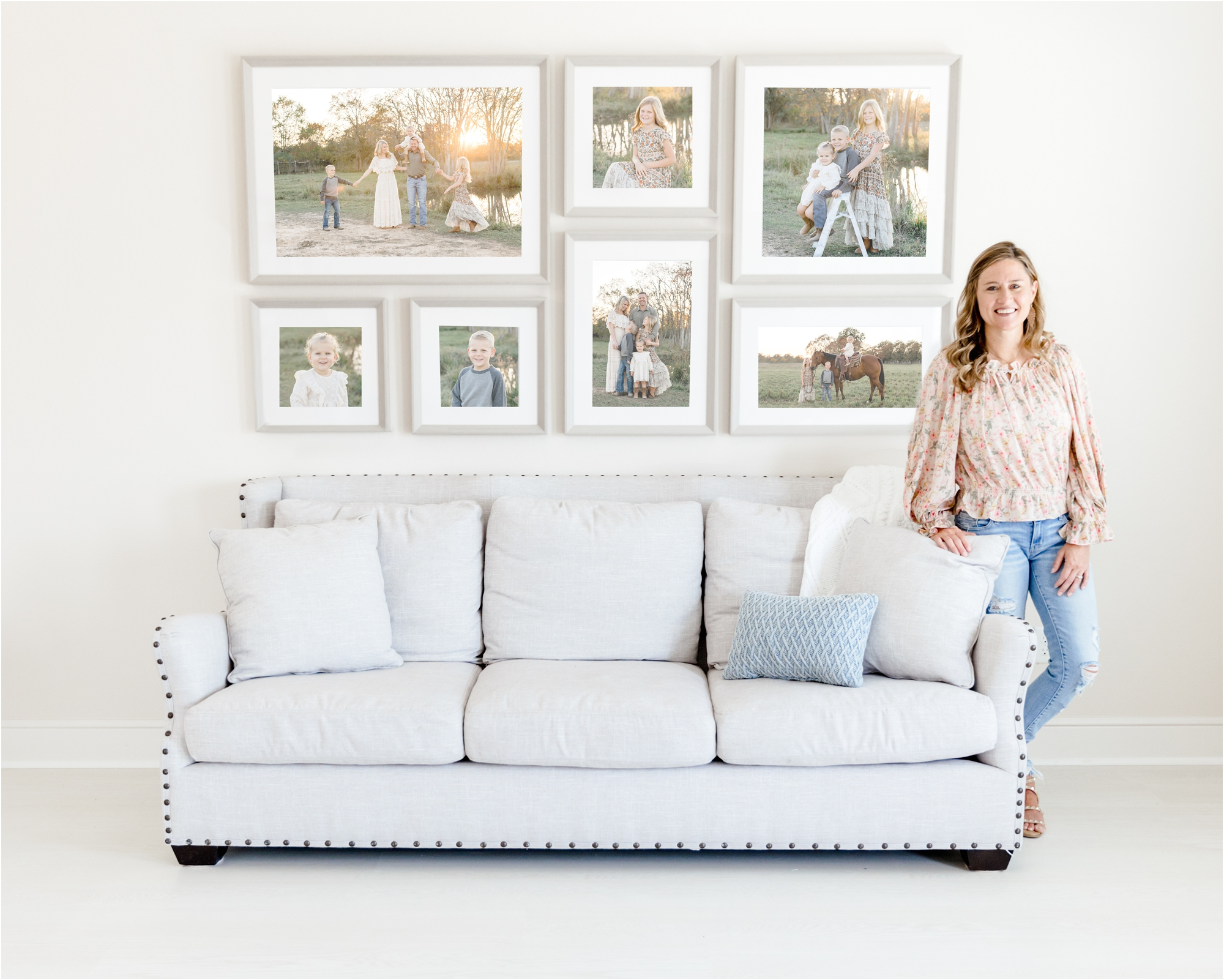 Kelly from Lifetime of Clicks Photography in her studio with large, custom wall art design above couch.
