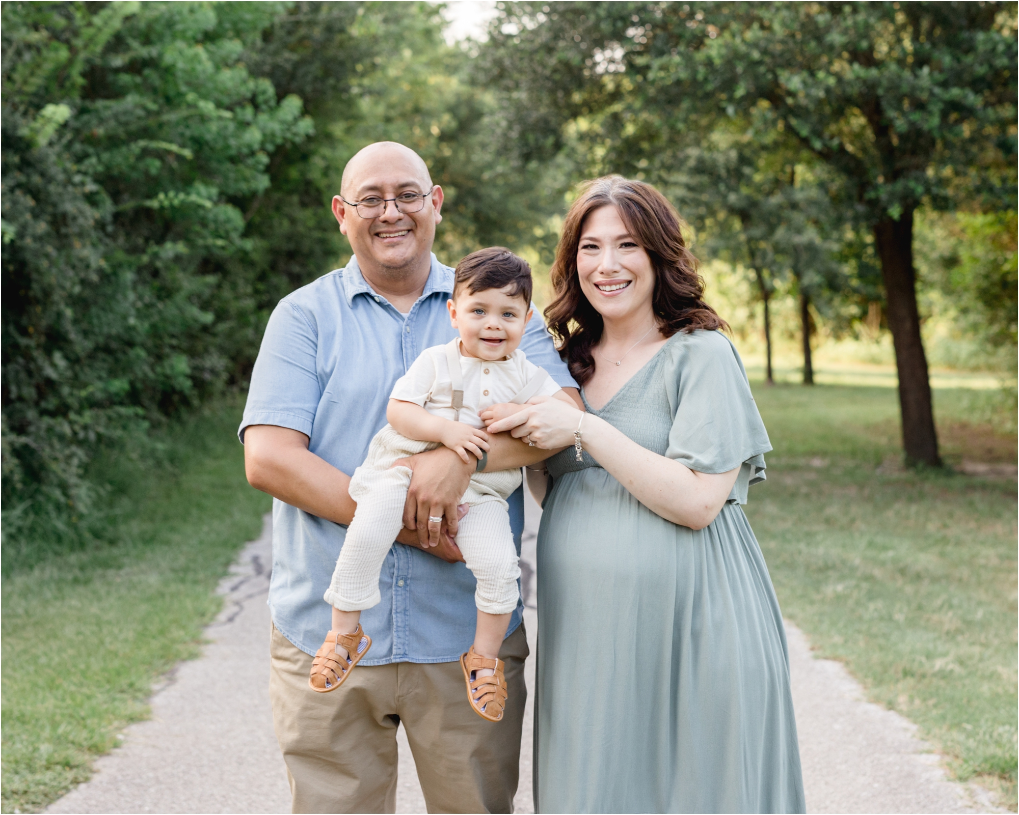 Family of three smiling at camera during maternity session in Houston park. Photo by Lifetime of Clicks Photography.