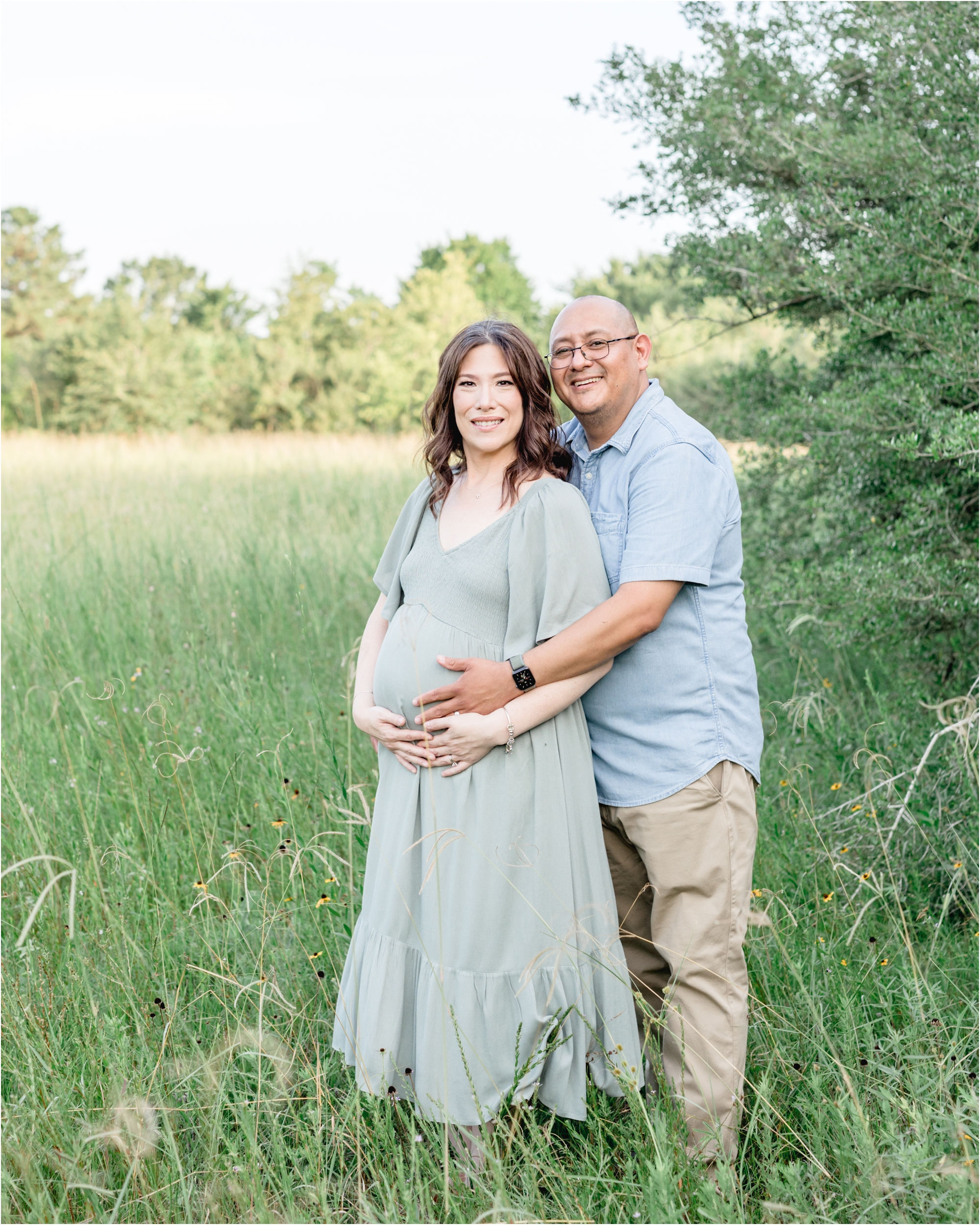 Mom and Dad smiling at camera during maternity photoshoot in Houston field. Photo by Lifetime of Clicks Photography.