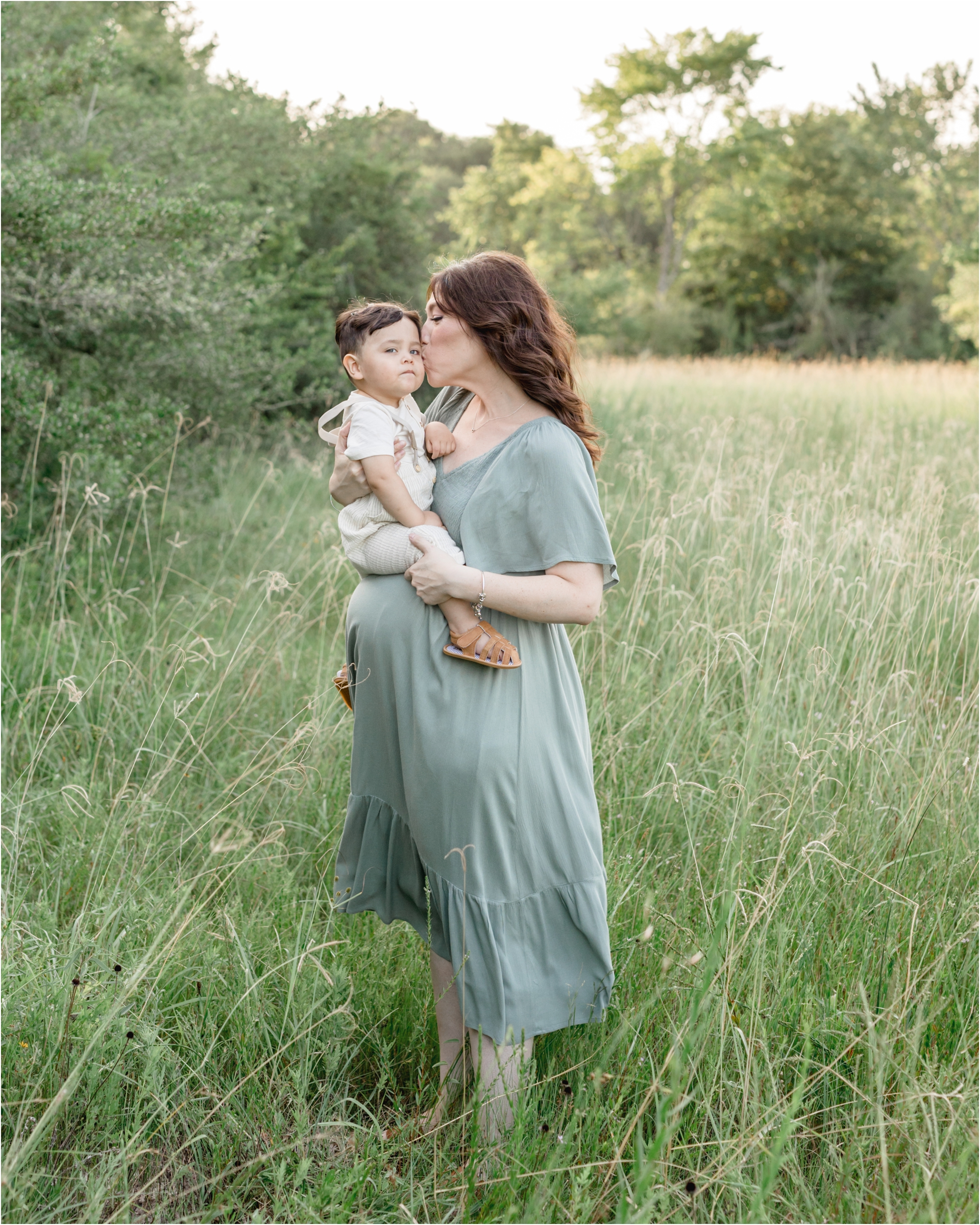Mom kisses toddler during field maternity photoshoot. Photo by Lifetime of Clicks Photography.