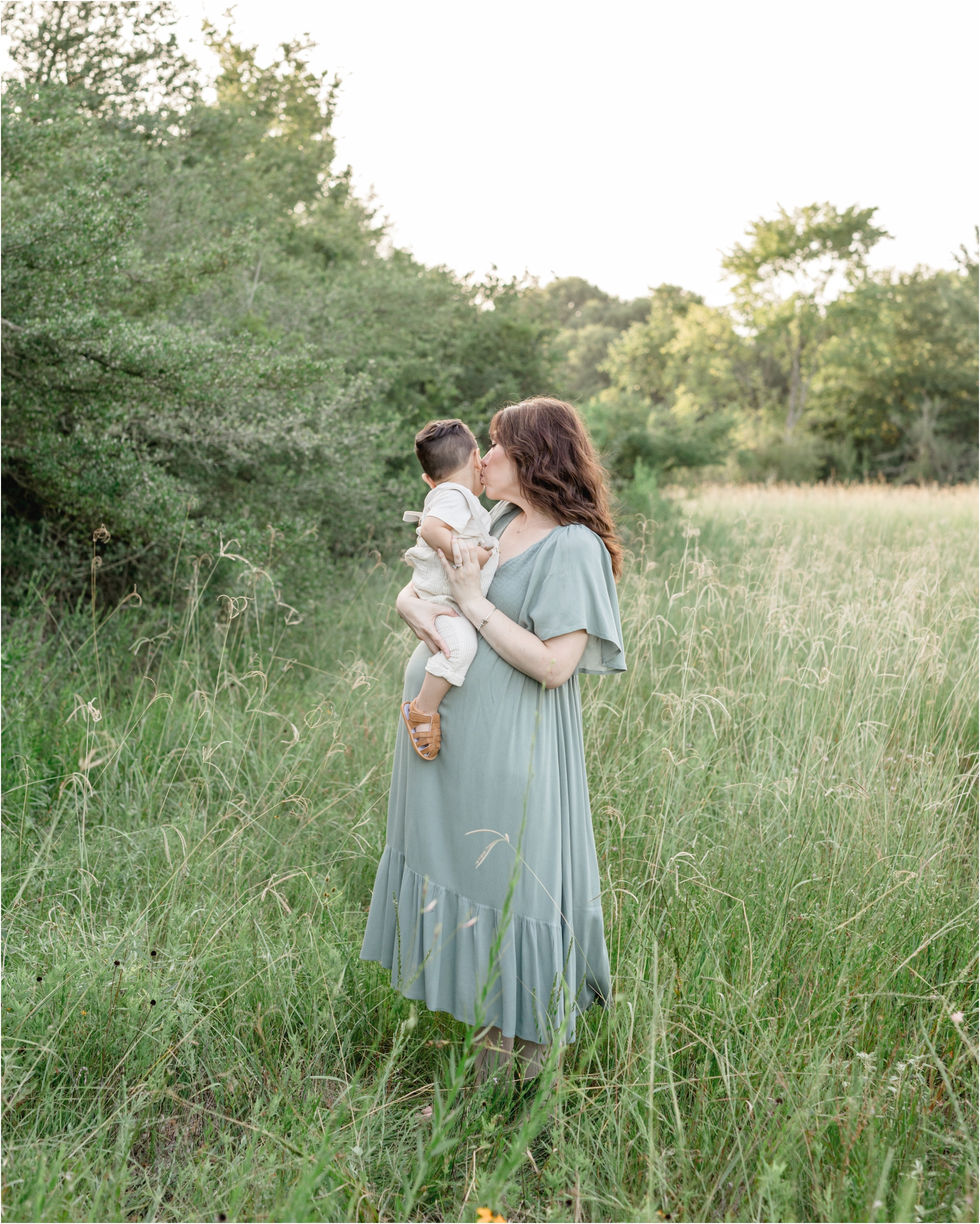 Dreamy maternity session in field with tall grass and Mama kissing toddler. Photo by Lifetime of Clicks Photography.
