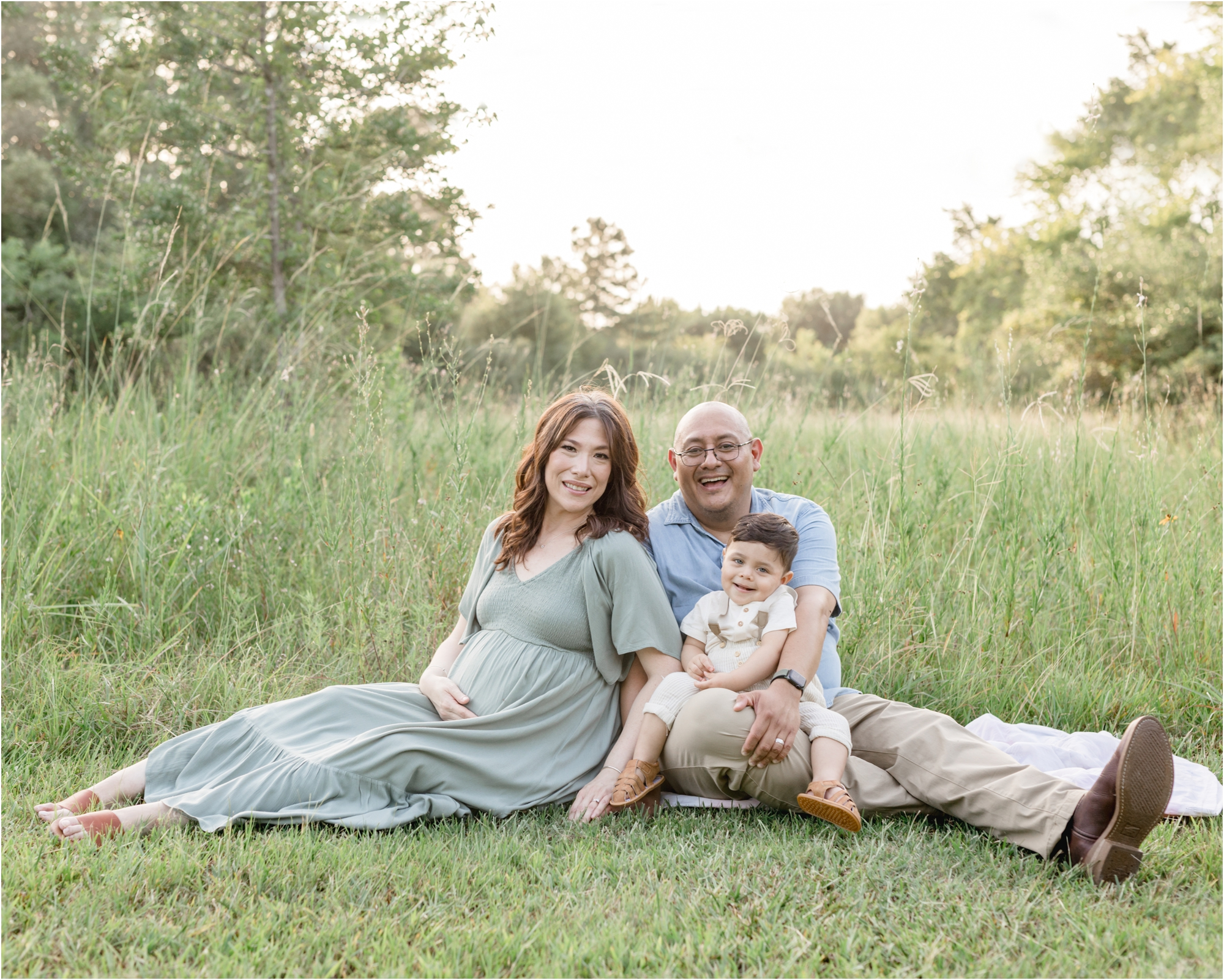 Family sitting near tall grass during portrait session with Houston photographer, Lifetime of Clicks Photography.