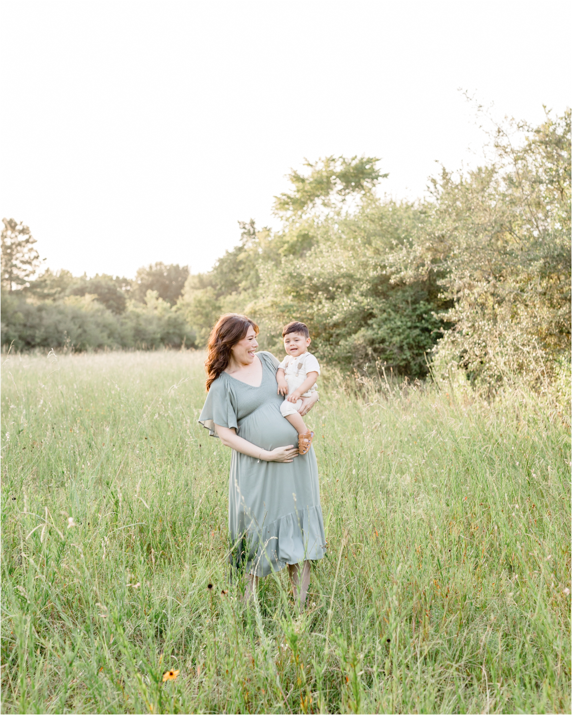 Mom talking through tall grass in field with toddler during maternity session with Lifetime of Clicks Photography.